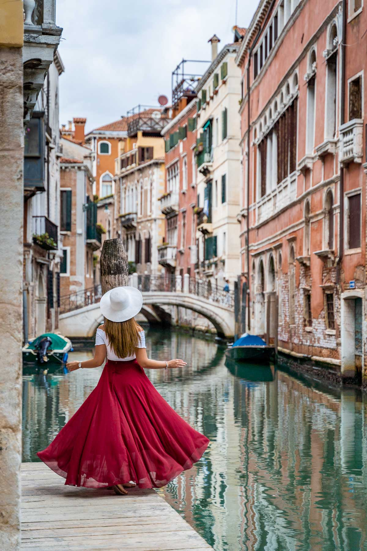 Girl in a red skirt twirling on a little pier along the canals in Venice