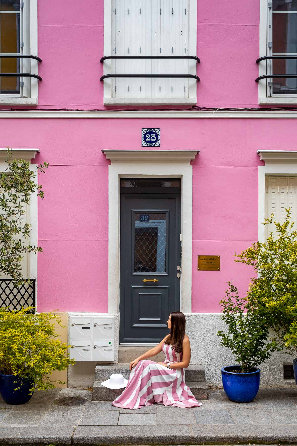 Girl in a pink-white dress sitting in front of a pink house at Rue Crémieux in Paris, France
