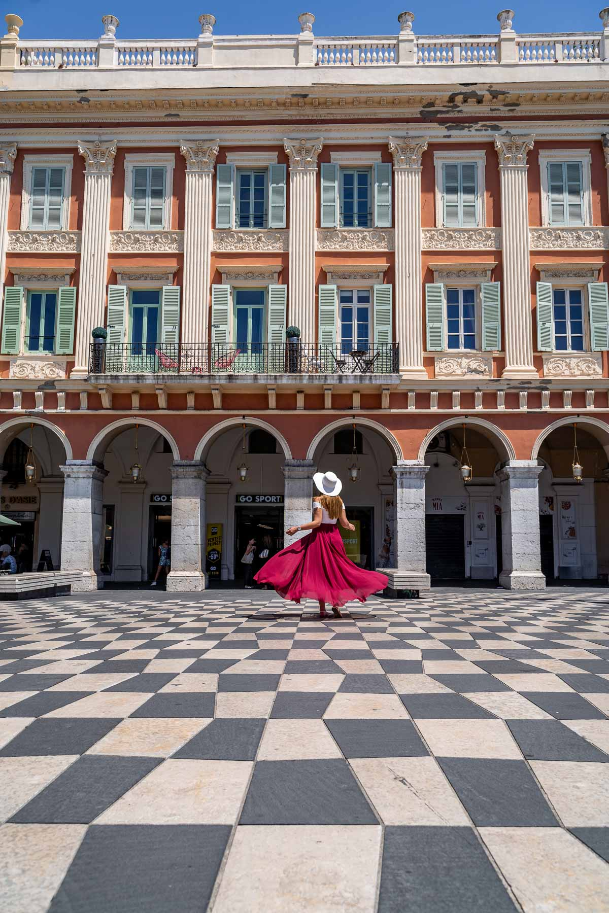 Girl in a red skirt twirling at Place Massena in Nice, France