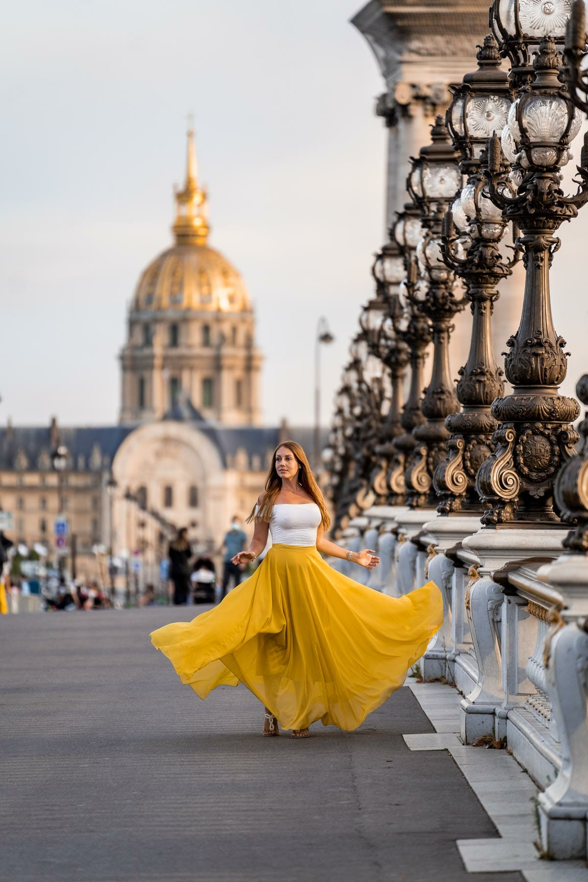 Girl in a pink dress twirling at Pont Alexandre III which is one of the most instagrammable places in Paris