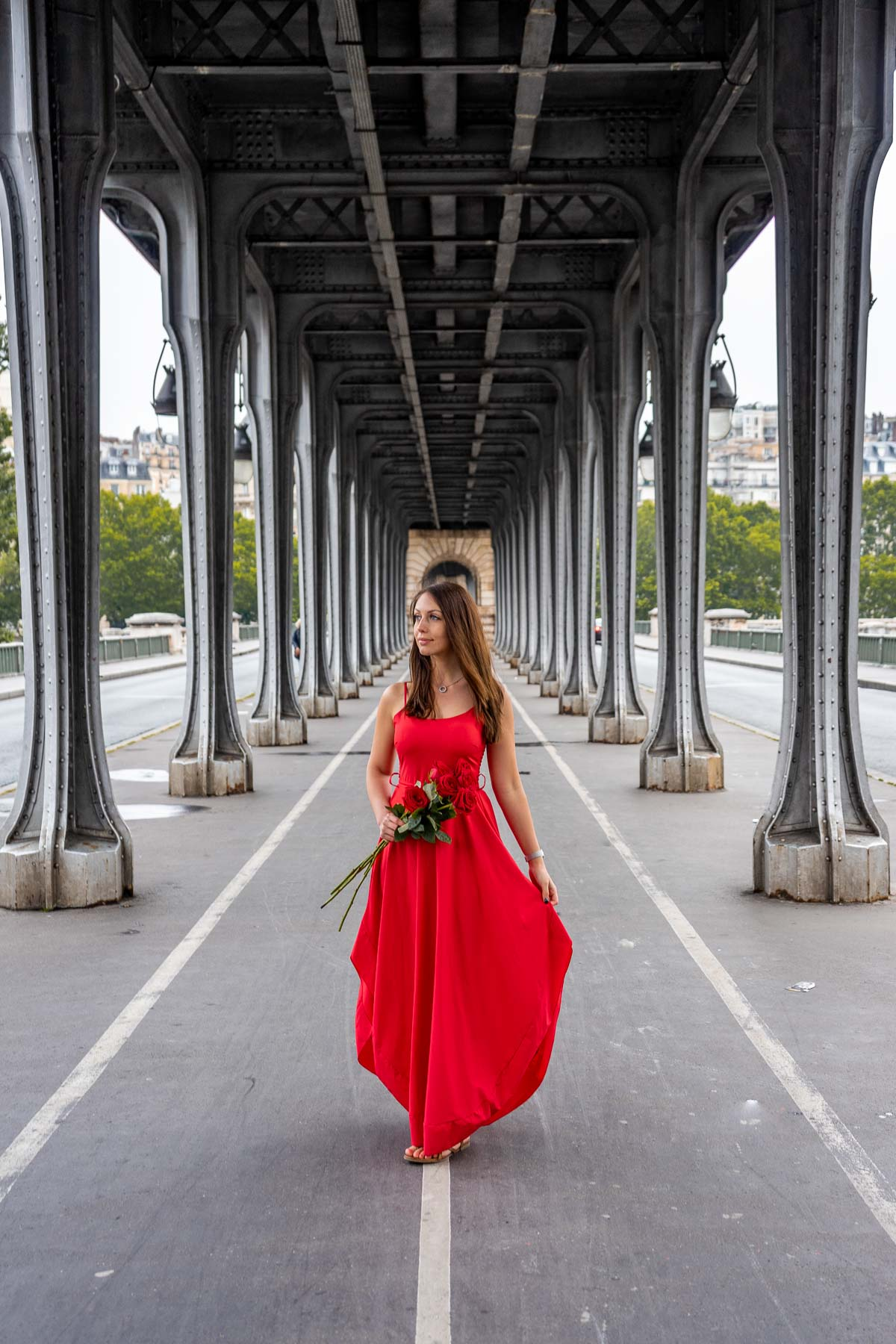 Girl in a red dress standing in the middle of Pont de bir-Hakeim with roses in her hand