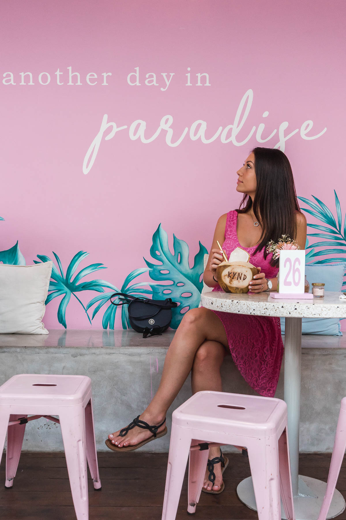 Girl in a pink dress standing in front of a pretty pink wall at Kynd Community in Seminyak, Bali