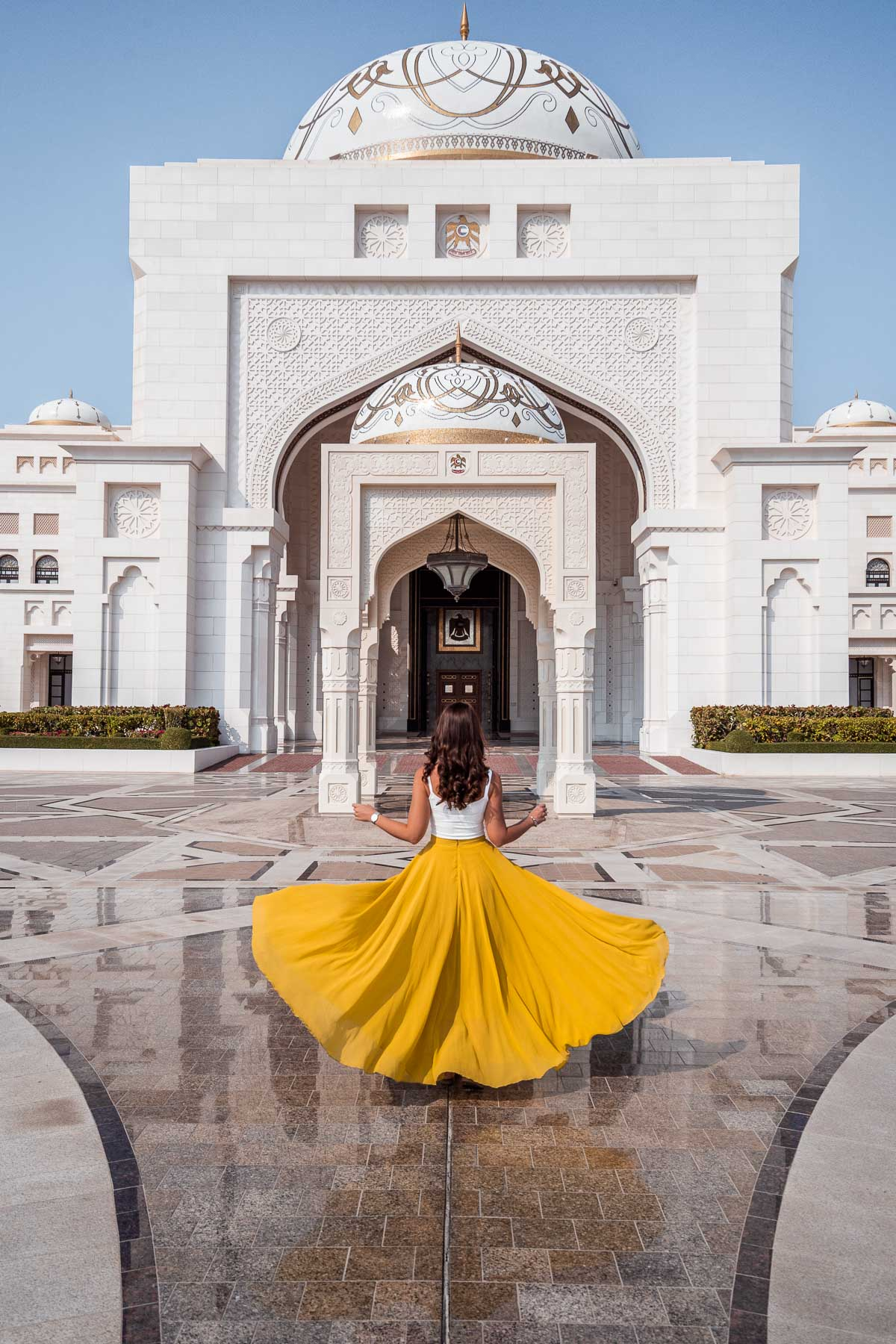 Girl in a yellow skirt twirling in front of Qasr Al Watan Palace in Abu Dhabi