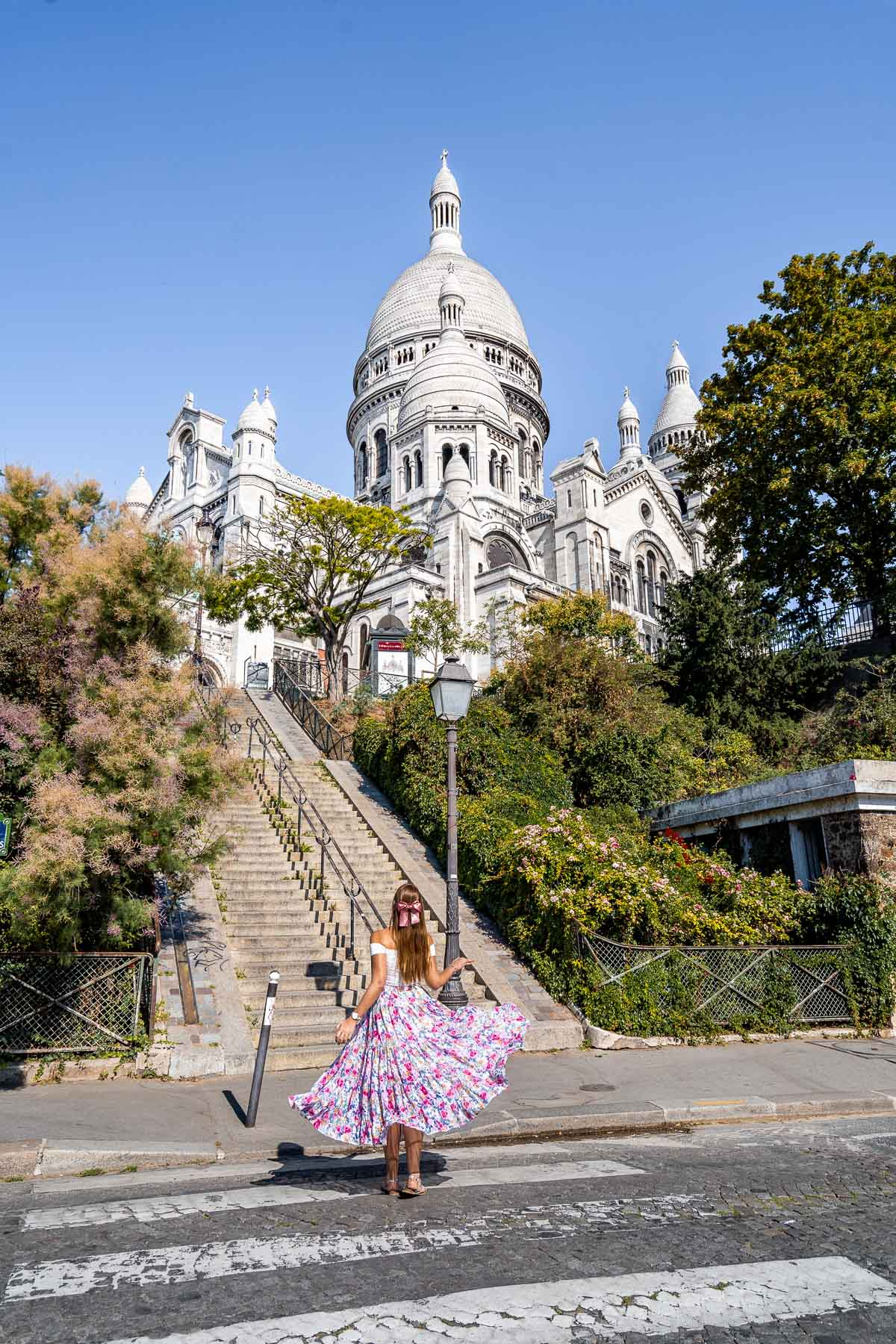 Girl in a pink floral skirt standing in front of the Sacré-Coeur Basilica in Paris