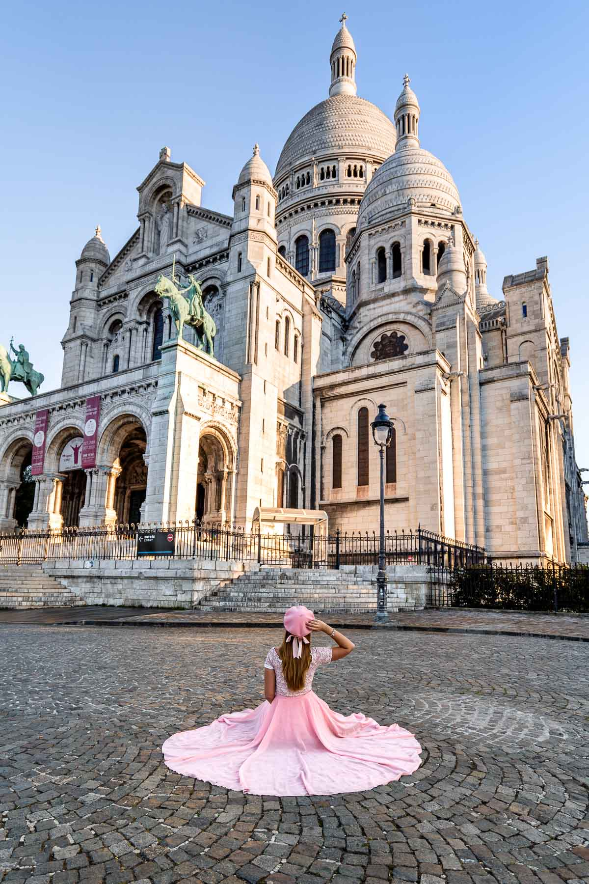 Girl in a pink dress sitting in front of the Sacré-Coeur Basilica in Paris