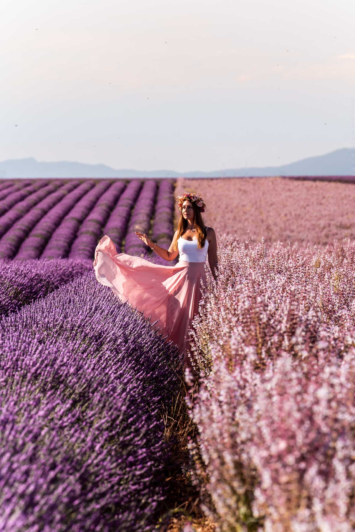 Girl in a pink skirt standing between the lavender fields and sage fields in Provence