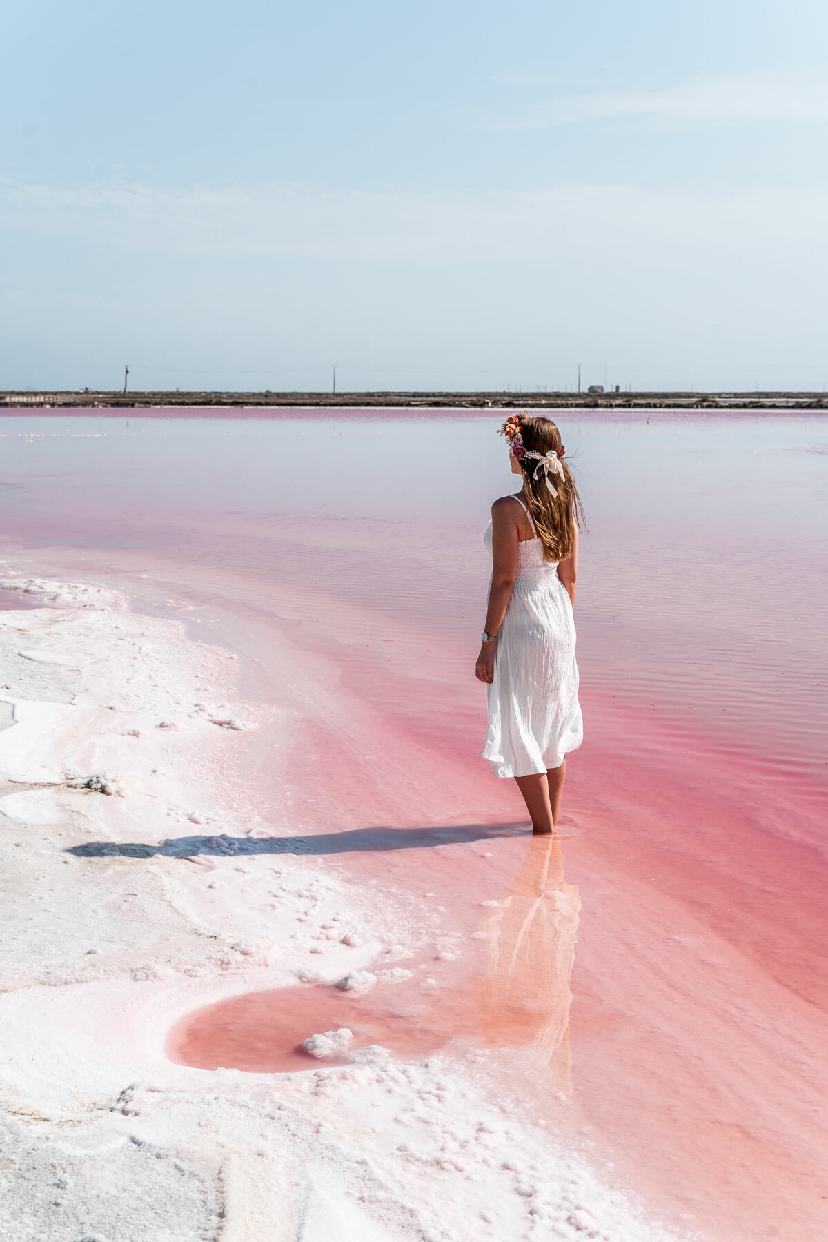 Girl in a white dress standing in a pink lake in France