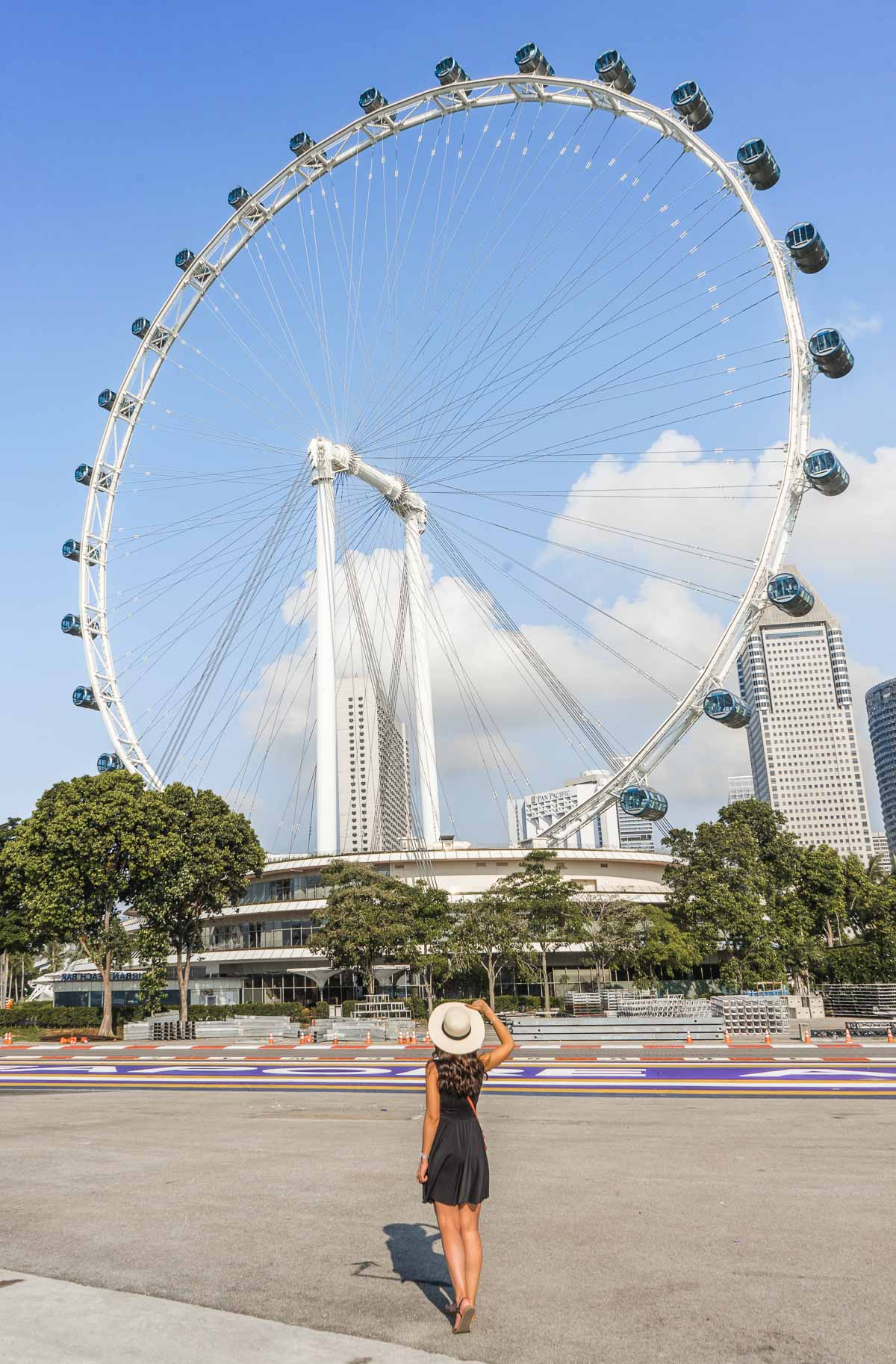 Girl in a black dress standing in front of the Singapore Flyer in Singapore