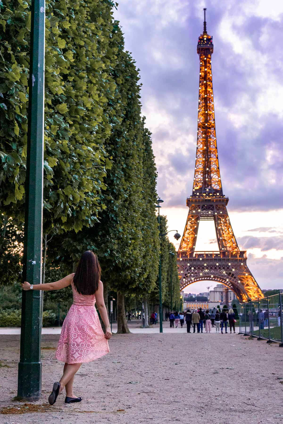 Girl in a pink dress watching the sparkling Eiffel Tower from Champ de Mars
