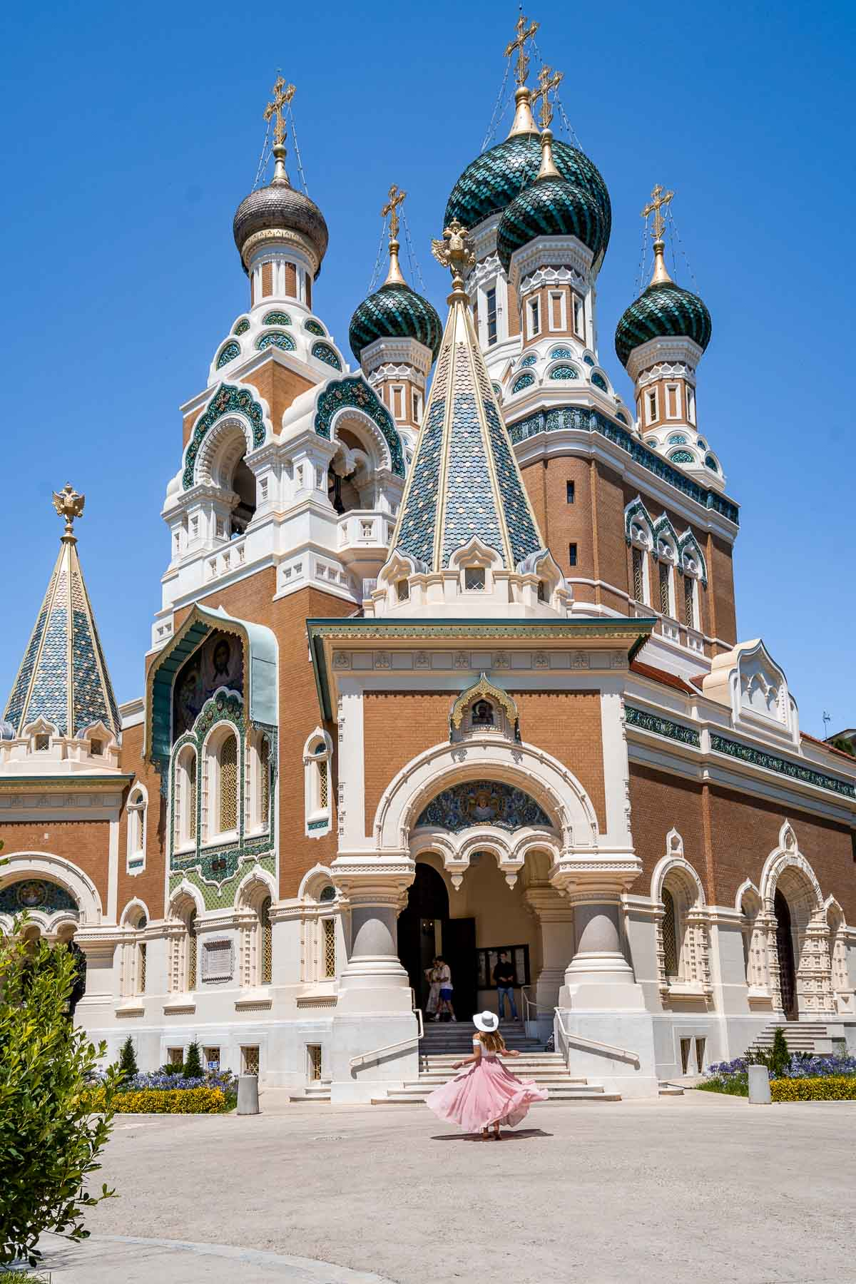 Girl in a pink skirt twirling in front of the St. Nicholas Russian Orthodox Cathedral in Nice, France