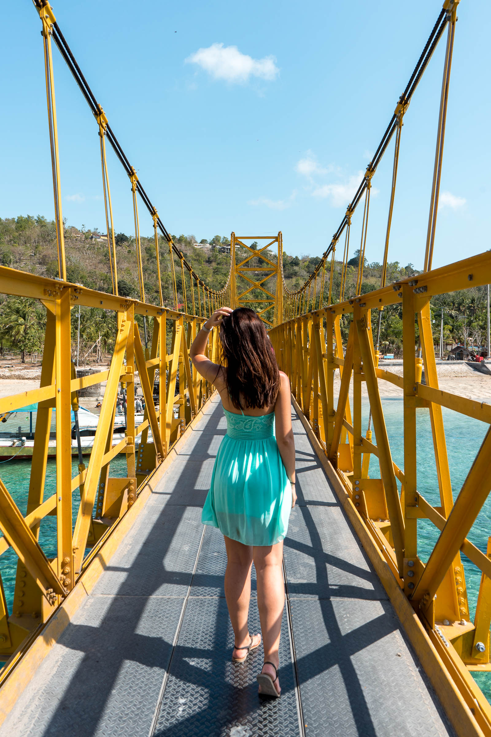 Girl in a blue dress standing on the Yellow bridge between Nusa Lembongan and Nusa Ceningan