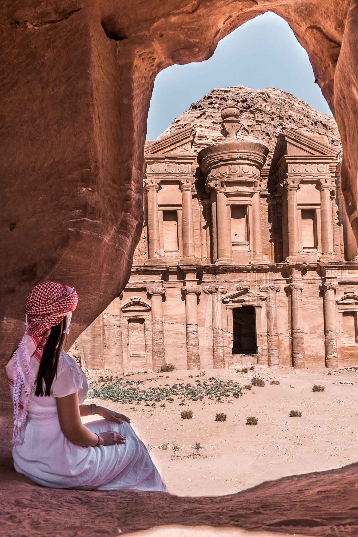 Girl in a white dress sitting in a cave, looking at the Al Deir Monastery in Petra, Jordan