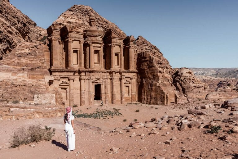 Girl in a white dress and a white-red keffiyeh standing in front of the Ad Deir Monastery in Petra, Jordan