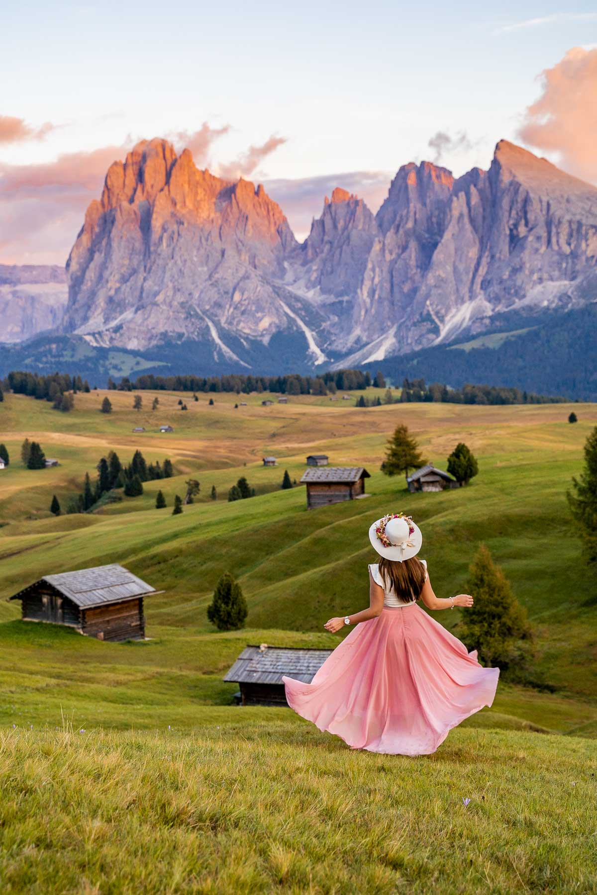 Girl in a pink skirt twirling at the meadows of Alpe di Siusi in the Dolomites