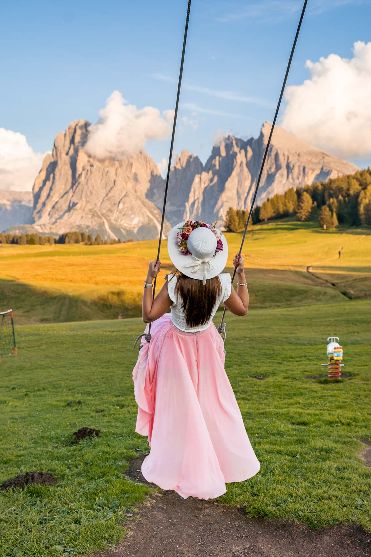Girl in a pink skirt swinging at Alpe di Siusi in the Dolomites