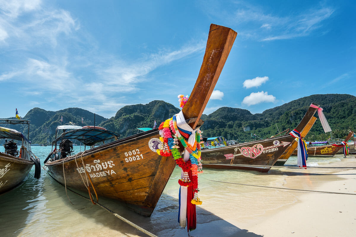 Long-tail boats on a sandy beach in Thailand