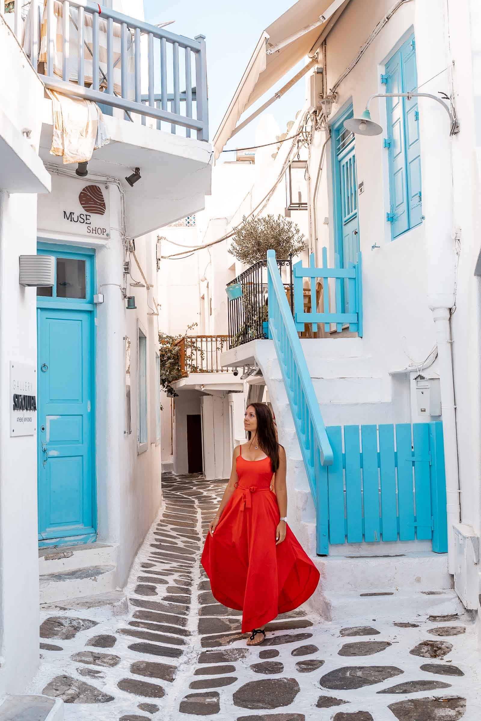 Girl in a red dress standing in the middle of a blue street in Mykonos