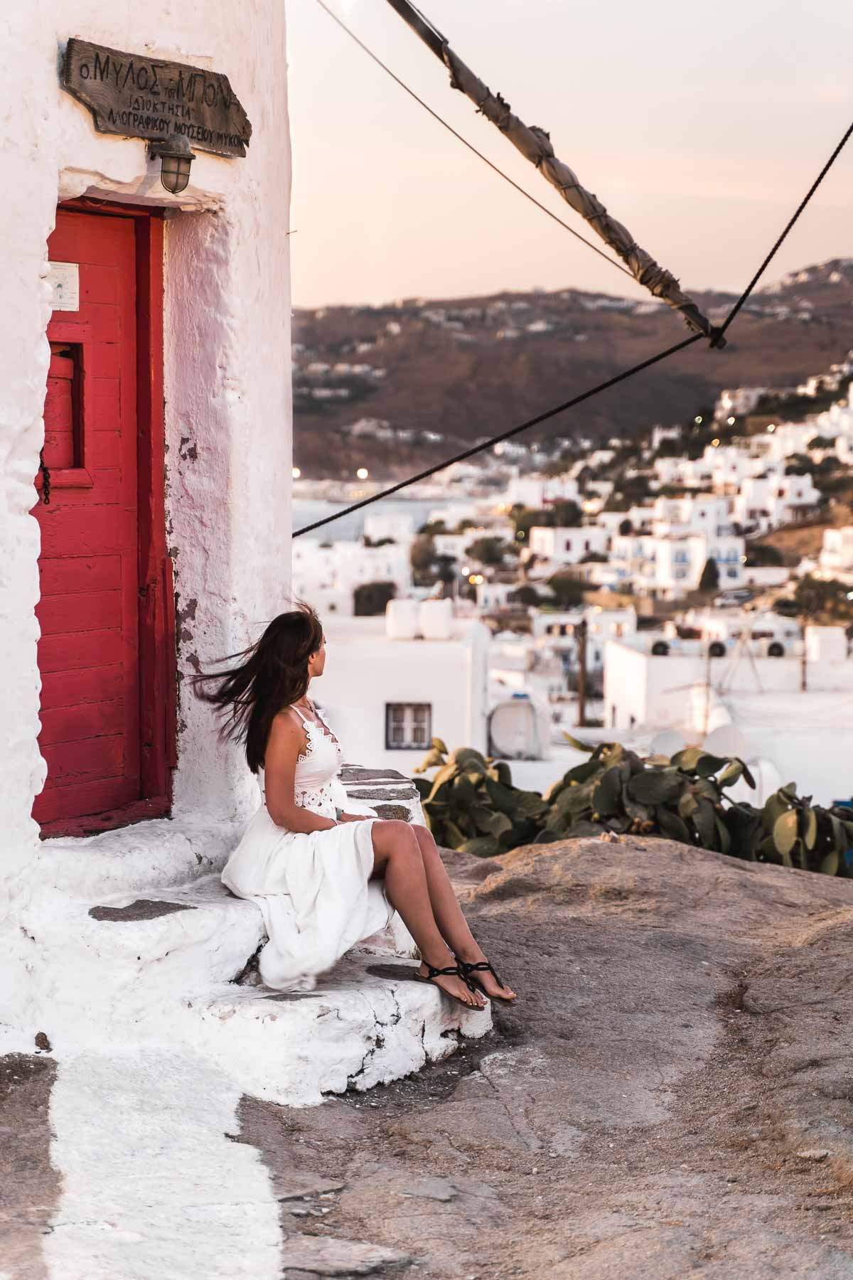 Girl in a white dress standing in front of Boni's Windmill, watching the sunset over Mykonos Town