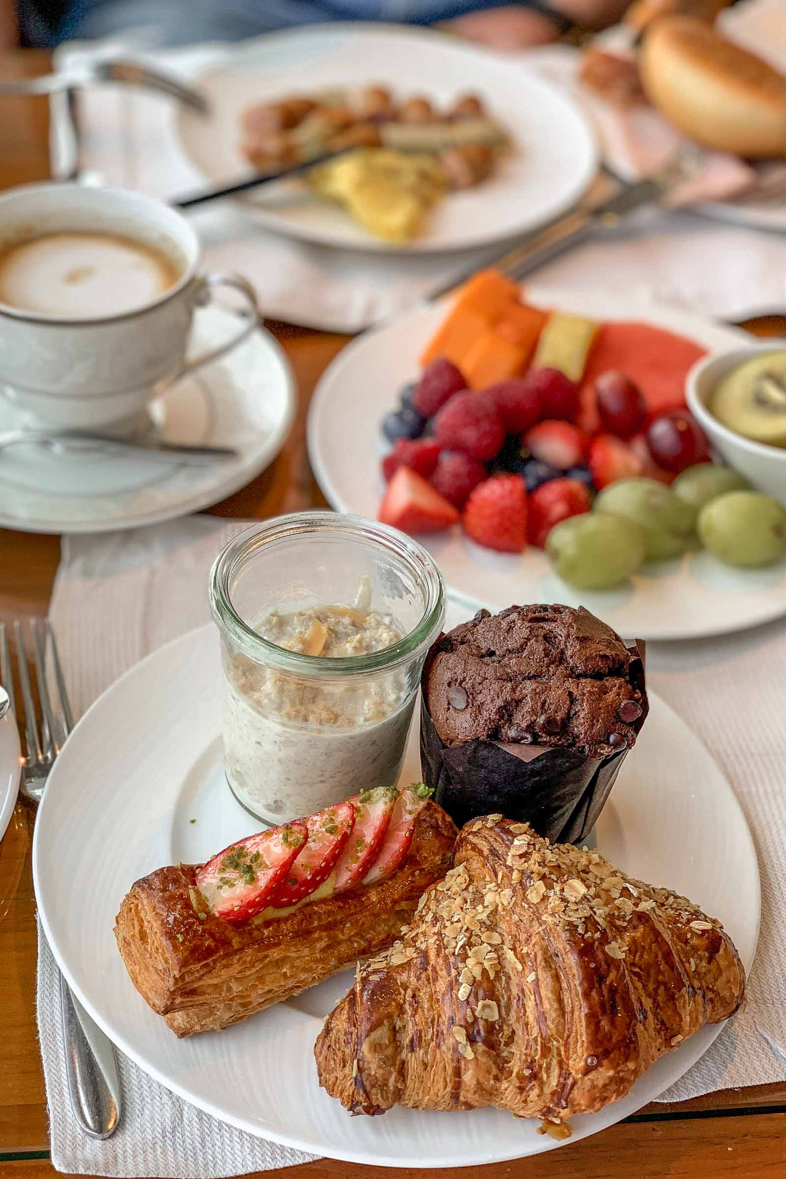 Breakfast with croissant, danish pastry, muffin, fruits and coffee