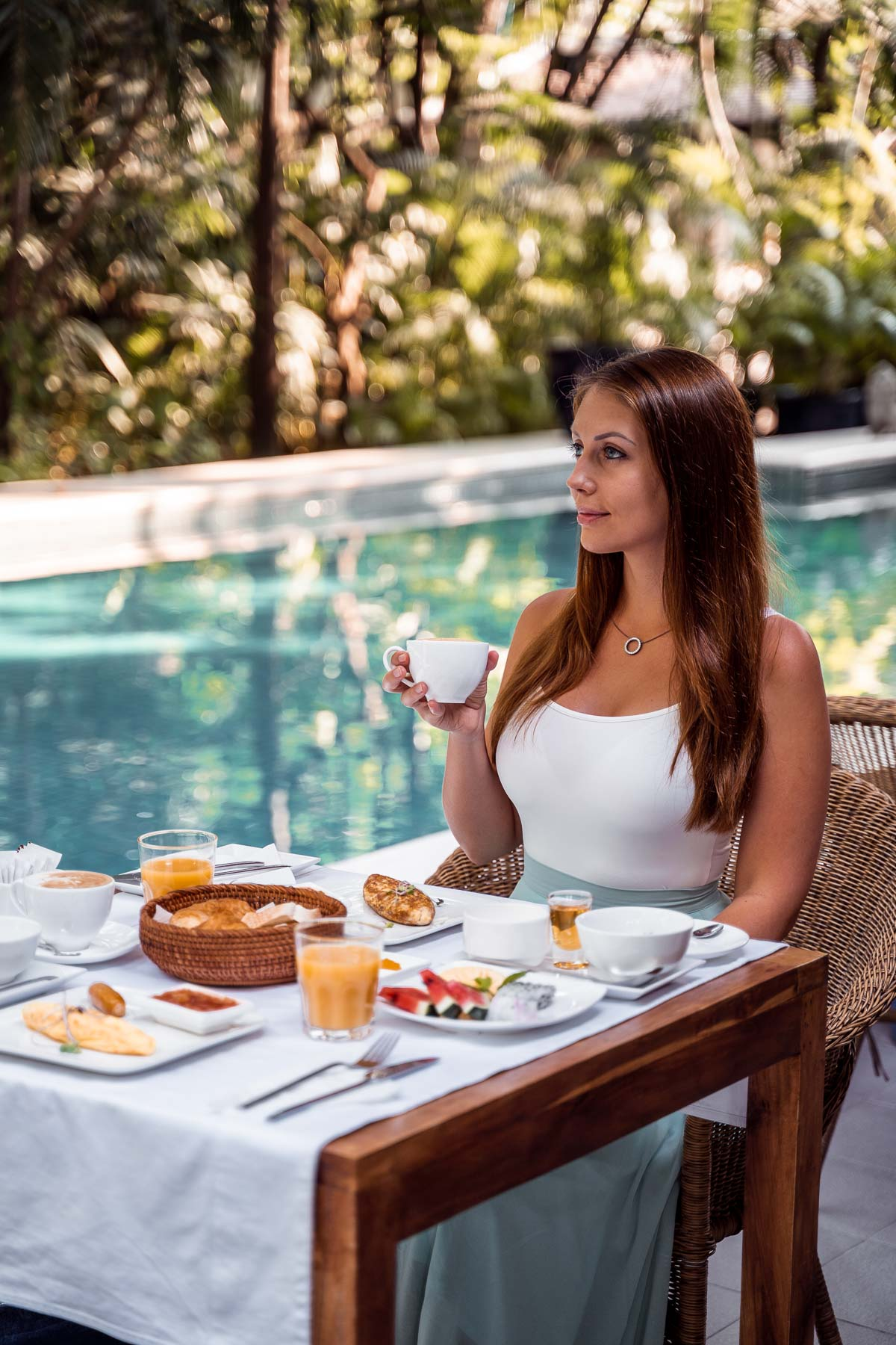 Girl in a white shirt having breakfast by the pool at Pavilion Phnom Penh