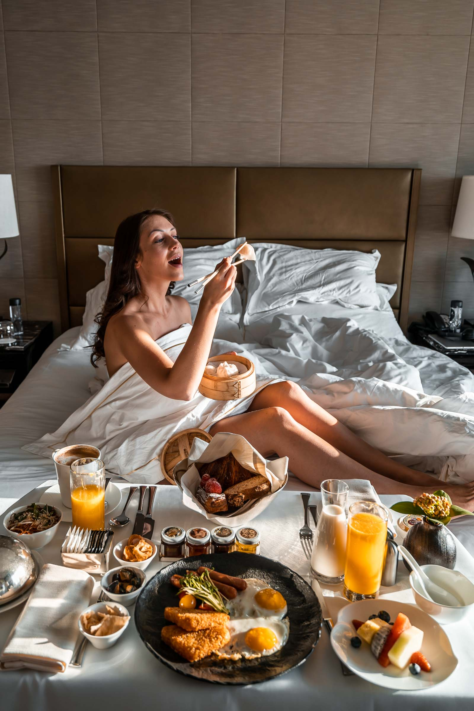 Girl sitting in the middle of the bed enjoying her breakfast