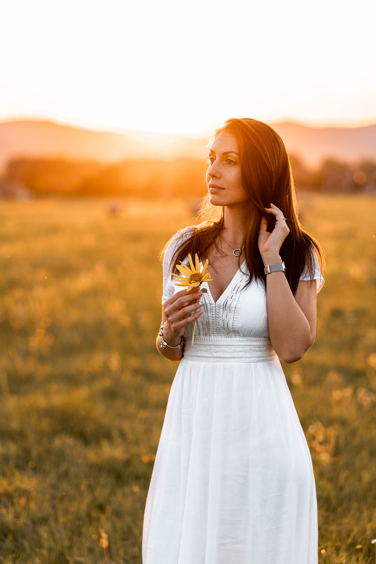 Girl in a white dress standing on a field at sunset