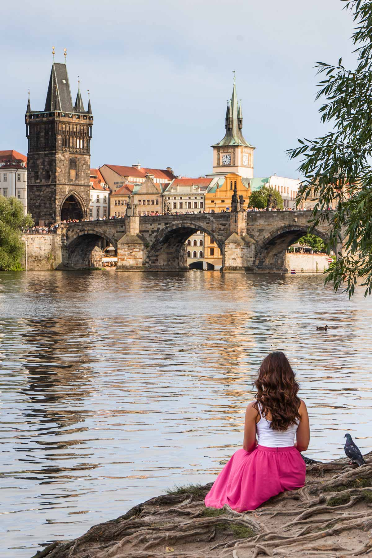 Girl in a pink skirt sitting by the river in Prague with the Charles Bridge in the background