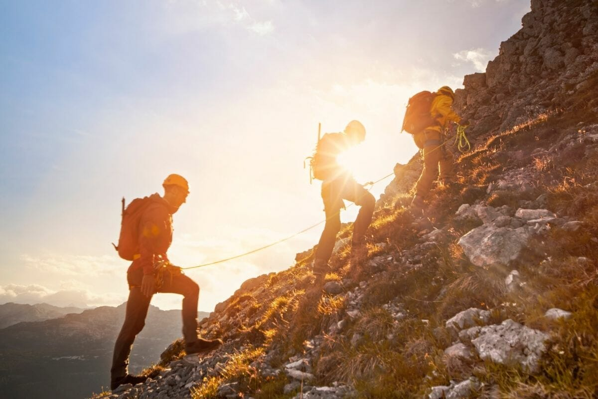 Three men hiking on a mountain in the morning light