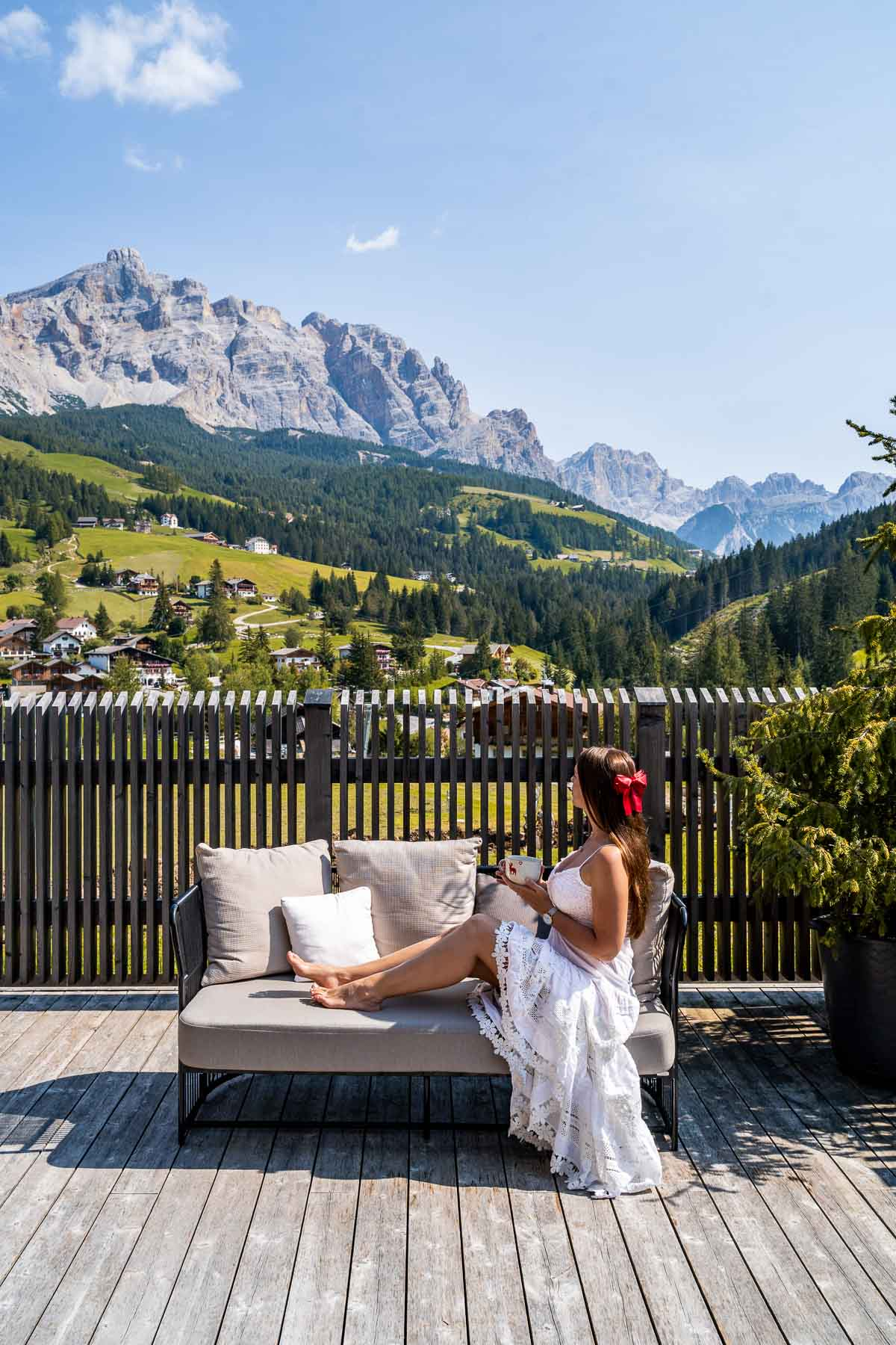 Girl in a white dress sitting on a sofa, looking at the mountain panorama at Hotel La Majun in the Dolomites