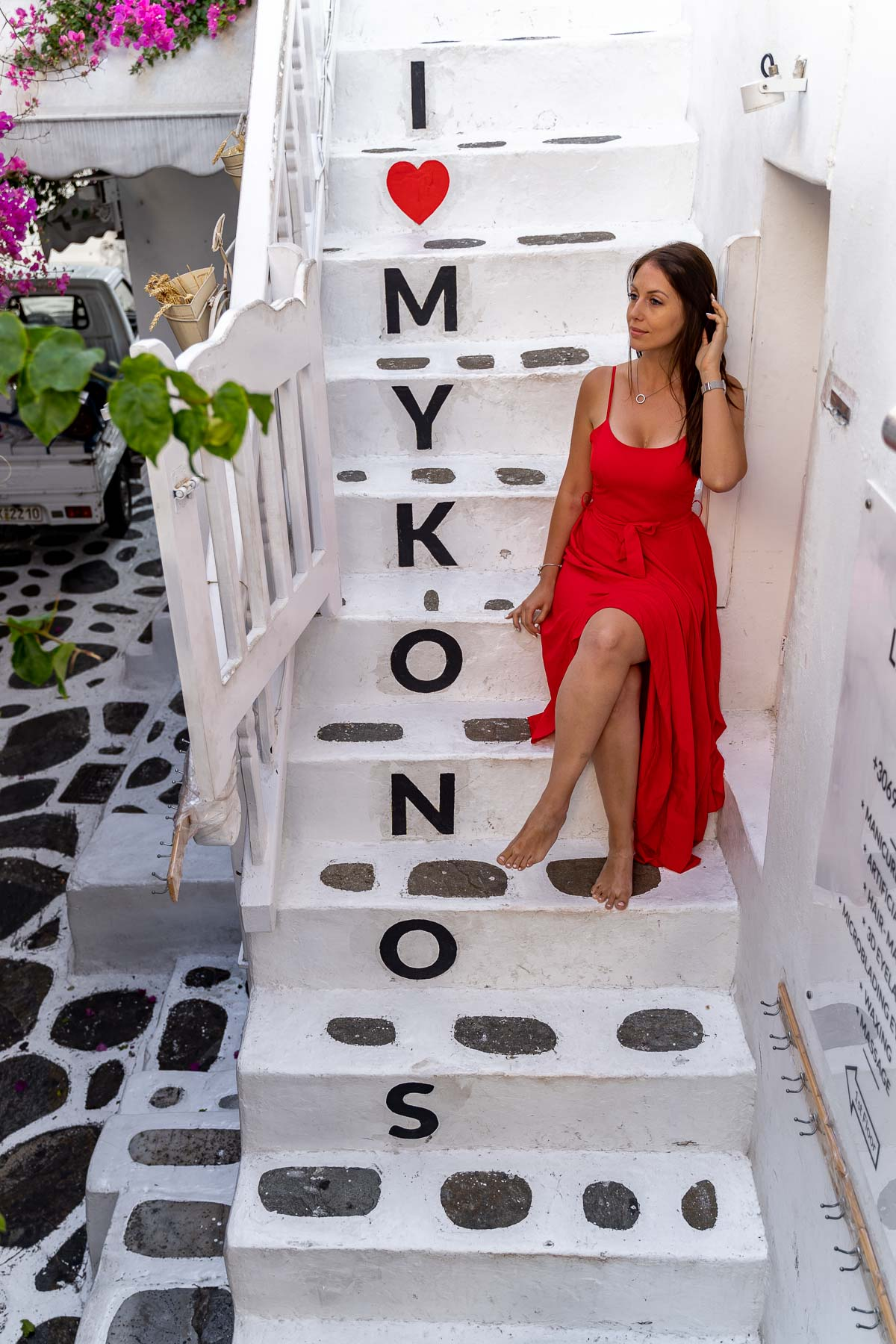 Girl in a red dress sitting on the I Love Mykonos stairway