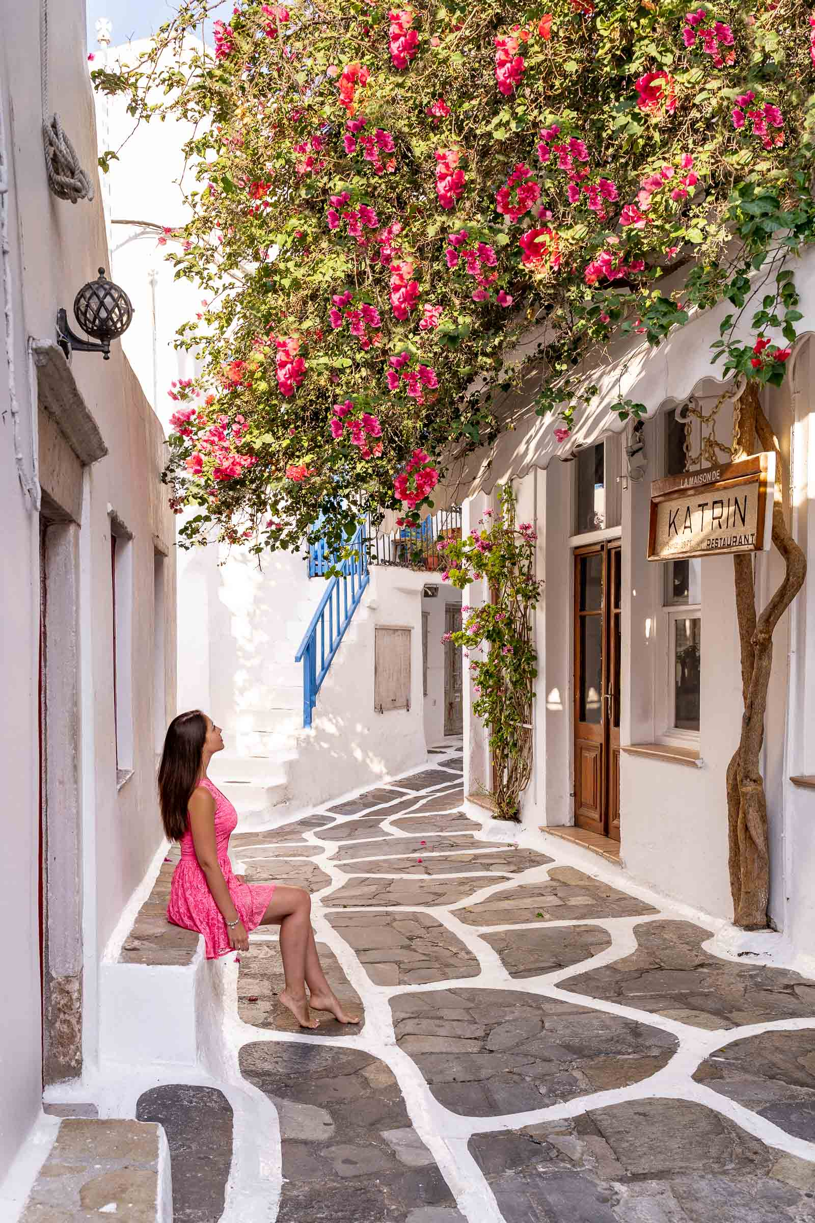 Girl in a pink dress sitting in front of La Maison de Katrin Restaurant which is one of the most instagrammable places in Mykonos