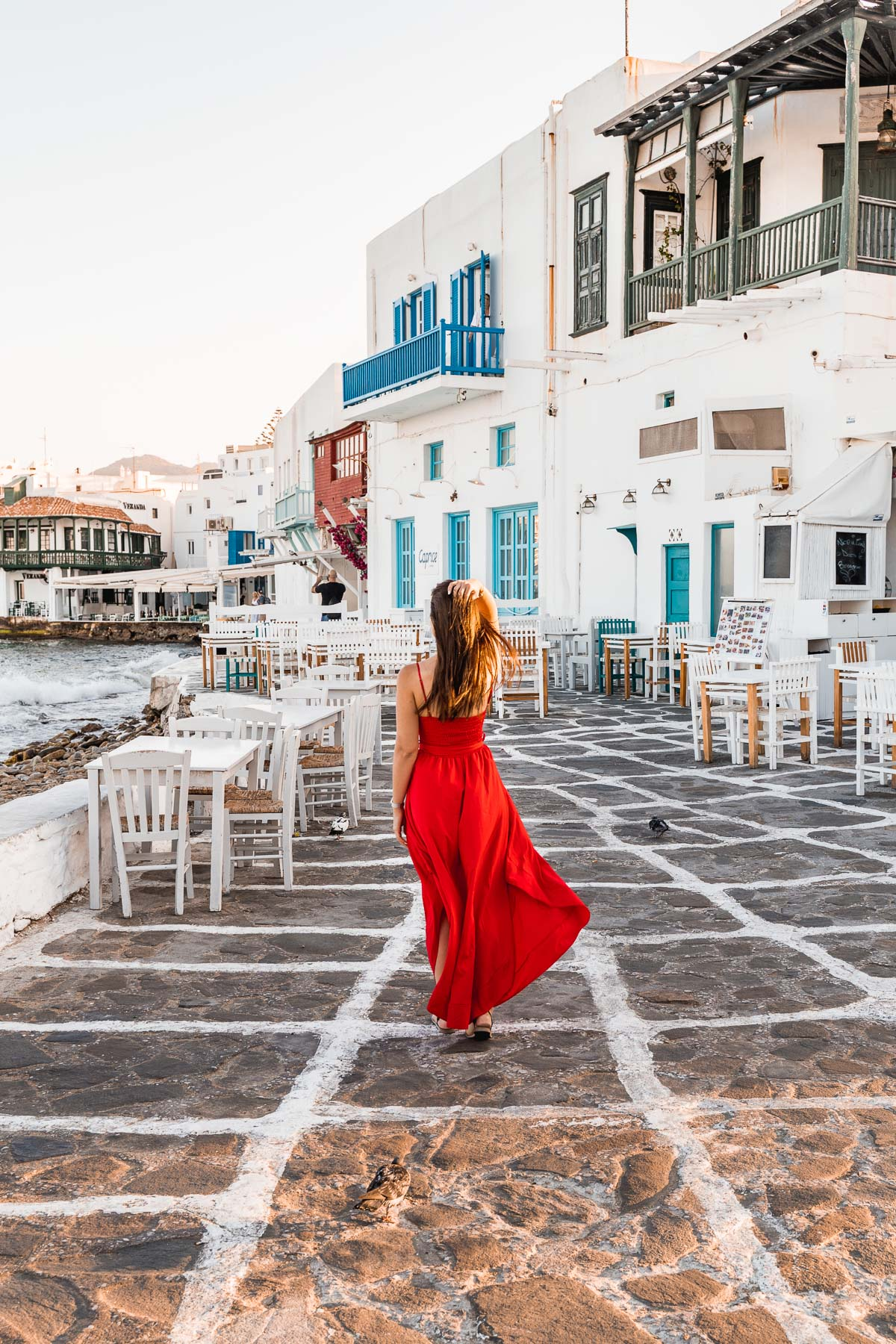 Girl in a red dress standing in the street at Little Venice in Mykonos Town