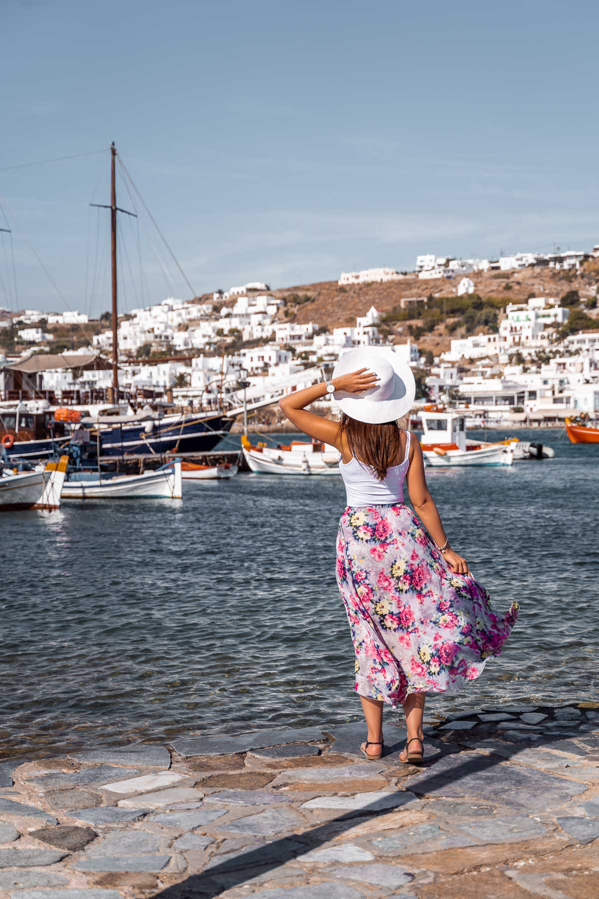 Girl in a purple floral dress standing in front of the Mykonos Harbour