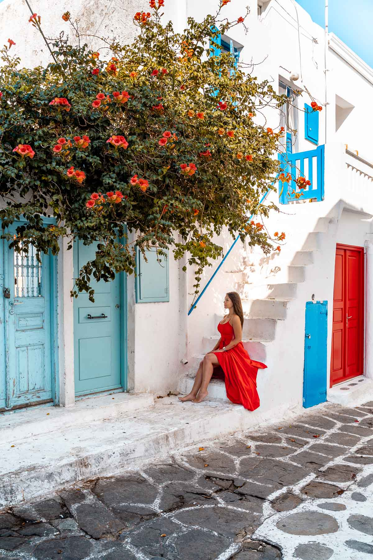 Girl in a red dress sitting on a stair at the turquoise door in Mykonos