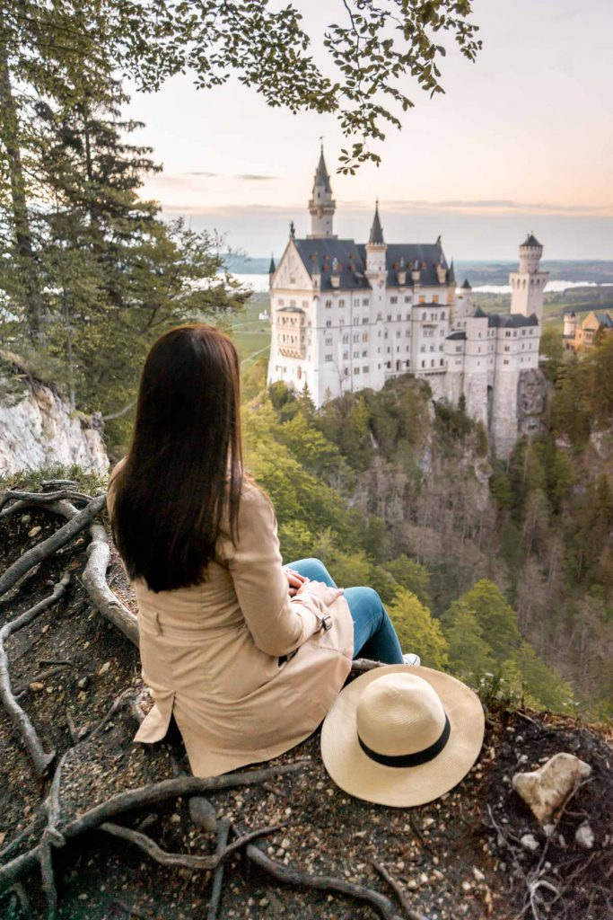 Girl in a trench coat sitting at the edge of a cliff, looking at the sunset over the Neuschwanstein Castle