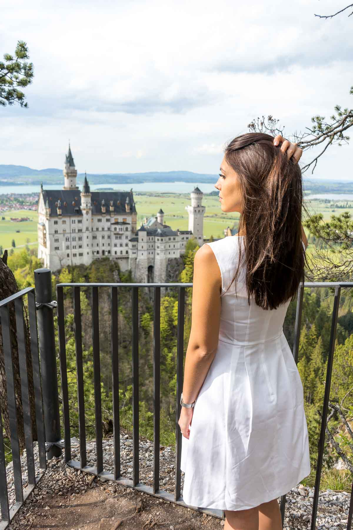 Girl in a white dress looking at the Neuschwanstein Castle from a viewpoint