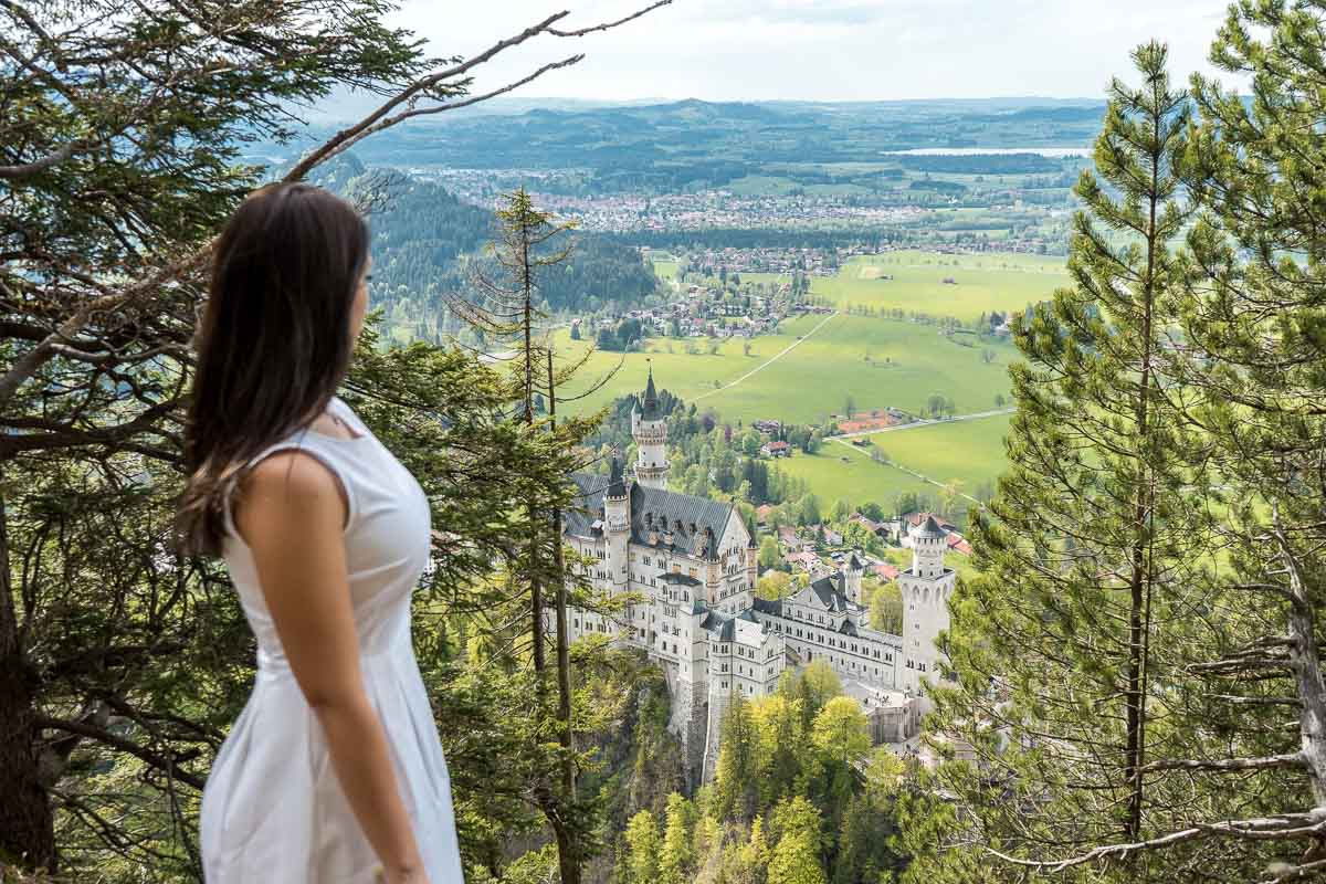 Girl in a white dress looking at the Neuschwanstein Castle from an upper viewpoint