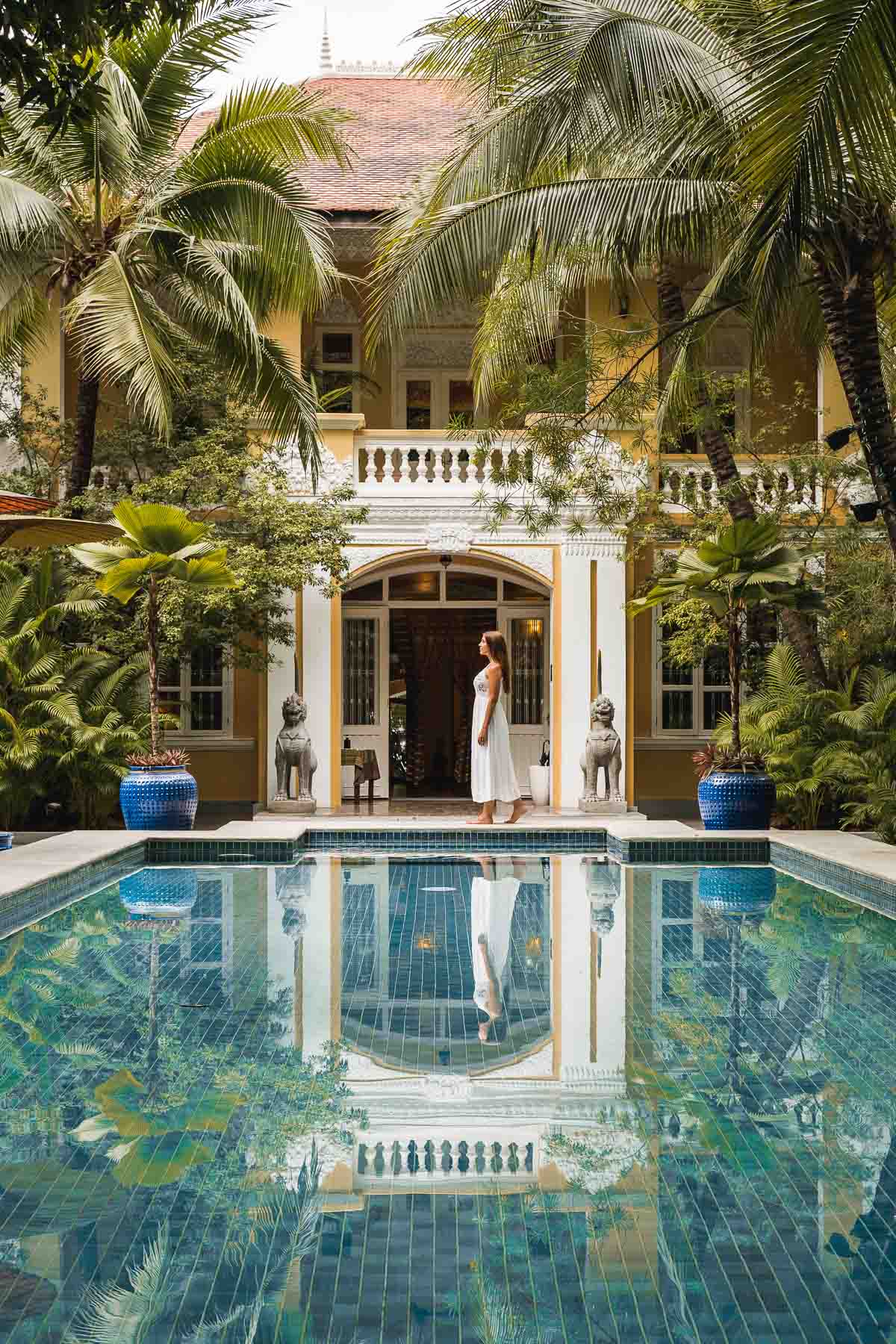Girl in a white dress standing in front of the Lush Pool at Pavilion Phnom Penh