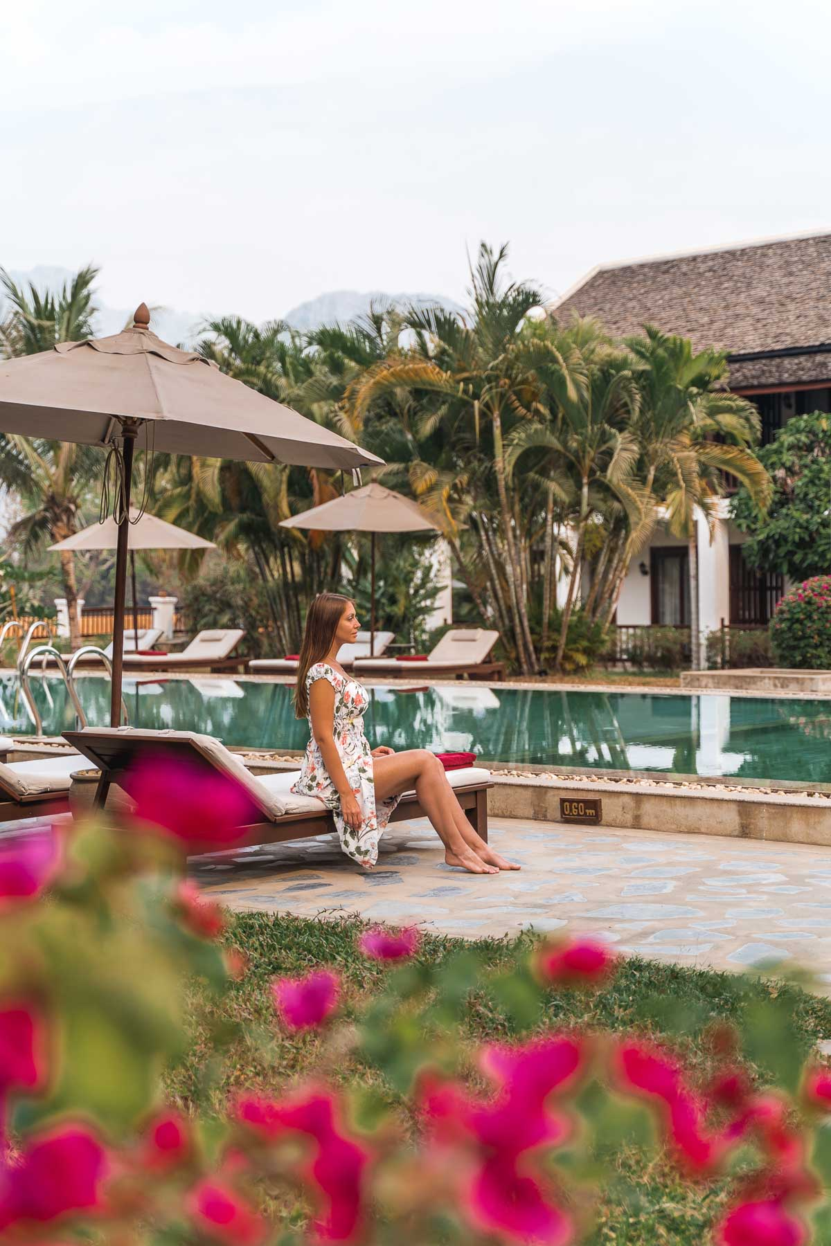 Girl in a floral dress sitting by the pool at the Riverside Boutique Resort Vang Vieng