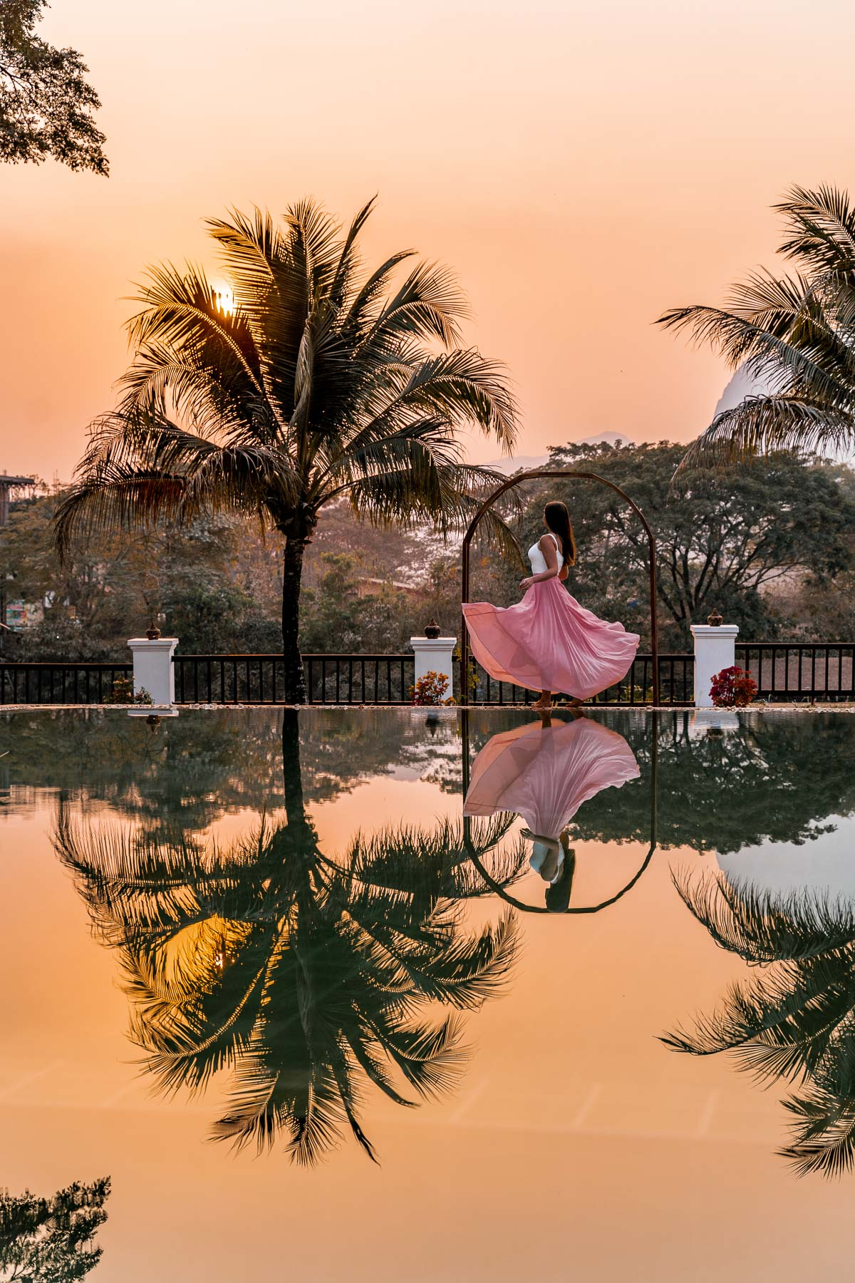 Girl in a pink dress standing at the pool in Riverside Boutique Resort Vang Vieng during sunset