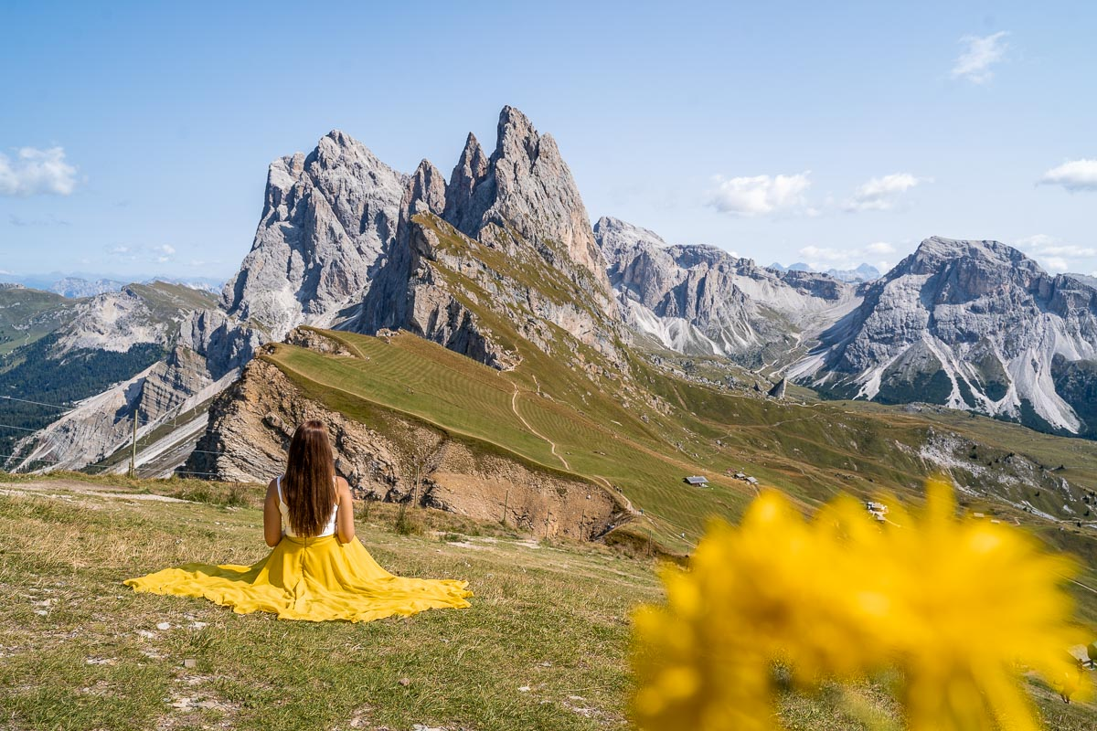 Girl in a yellow skirt sitting at Seceda ridgeline in the Dolomites, Italy