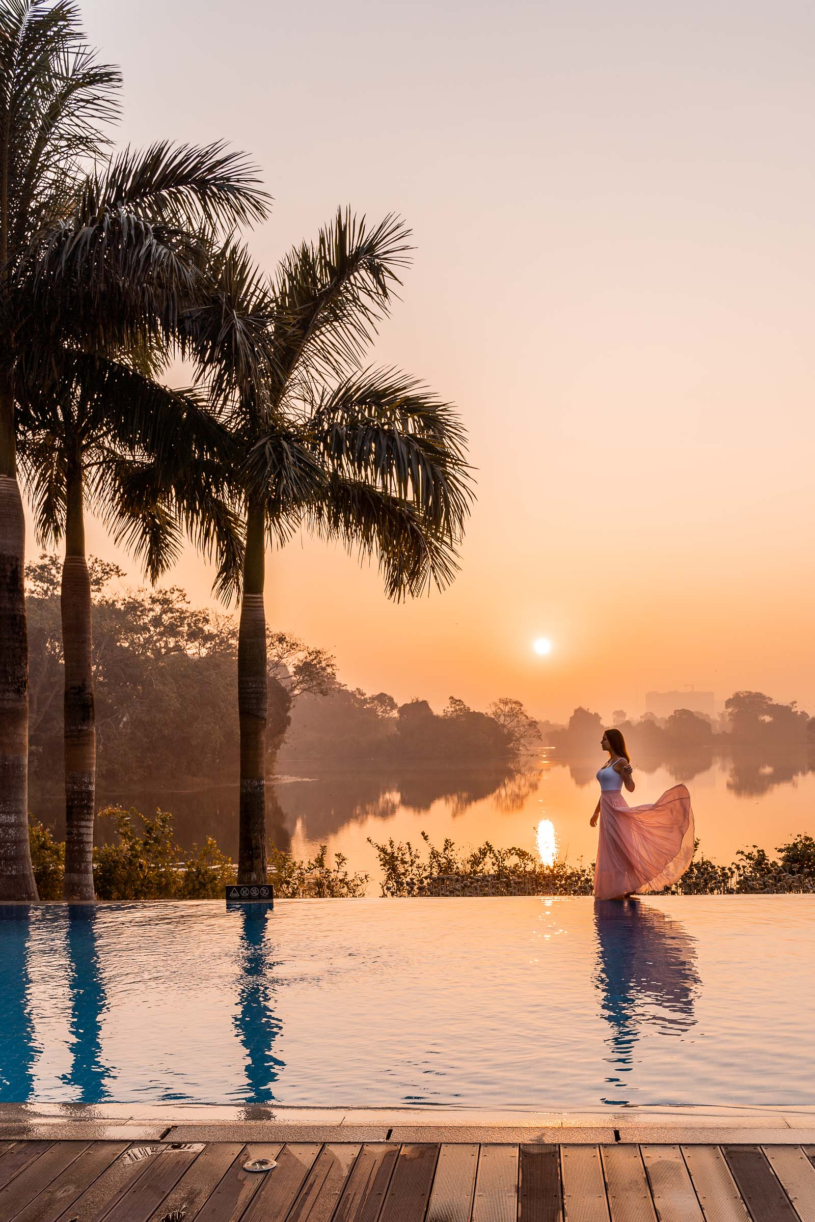 Girl in a pink dress standing by the pool at sunrise in Lotte Hotel Yangon