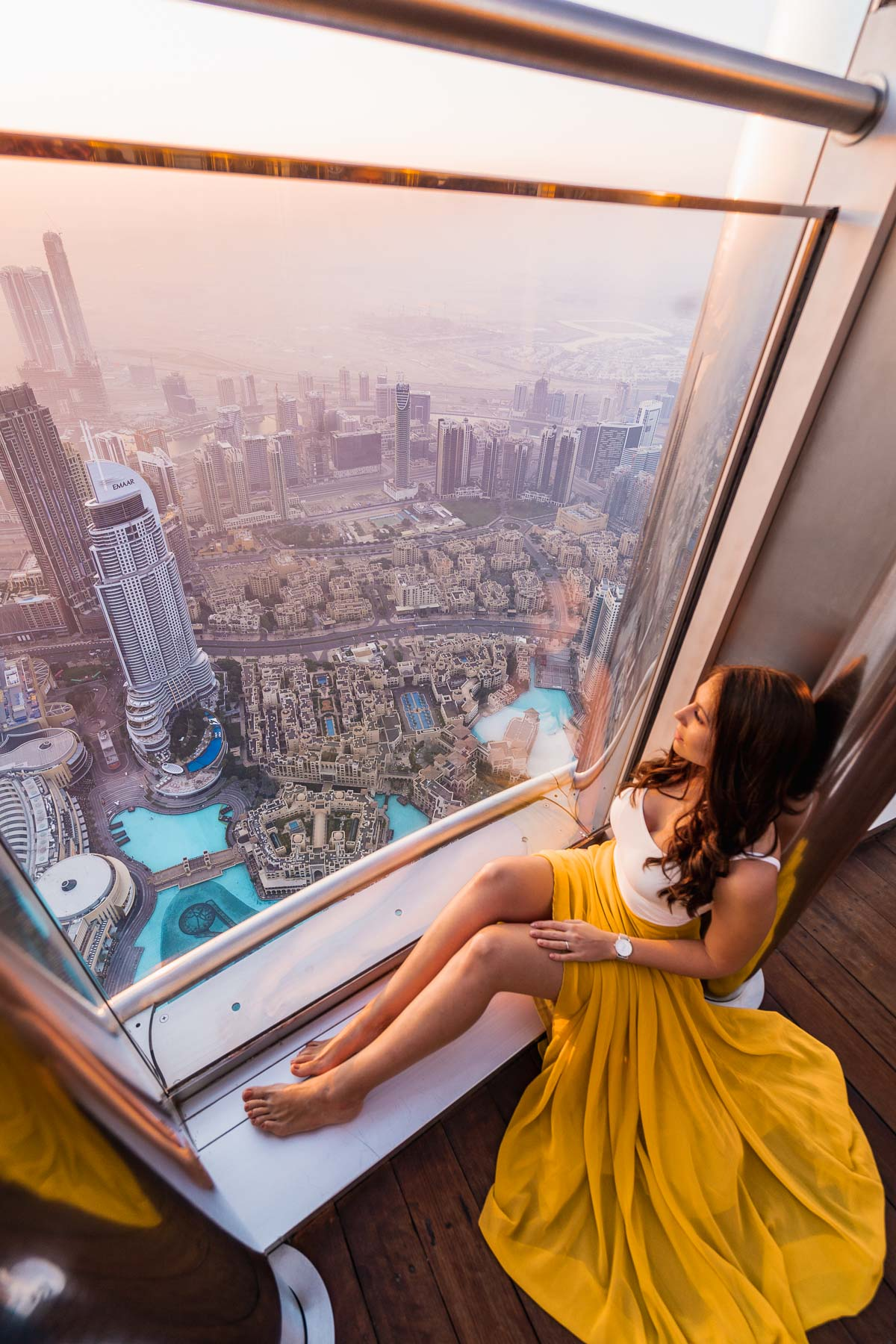 Girl in a yellow skirt sitting in front of a window in the Burj Khalifa at sunrise with the Dubai skyline in the background