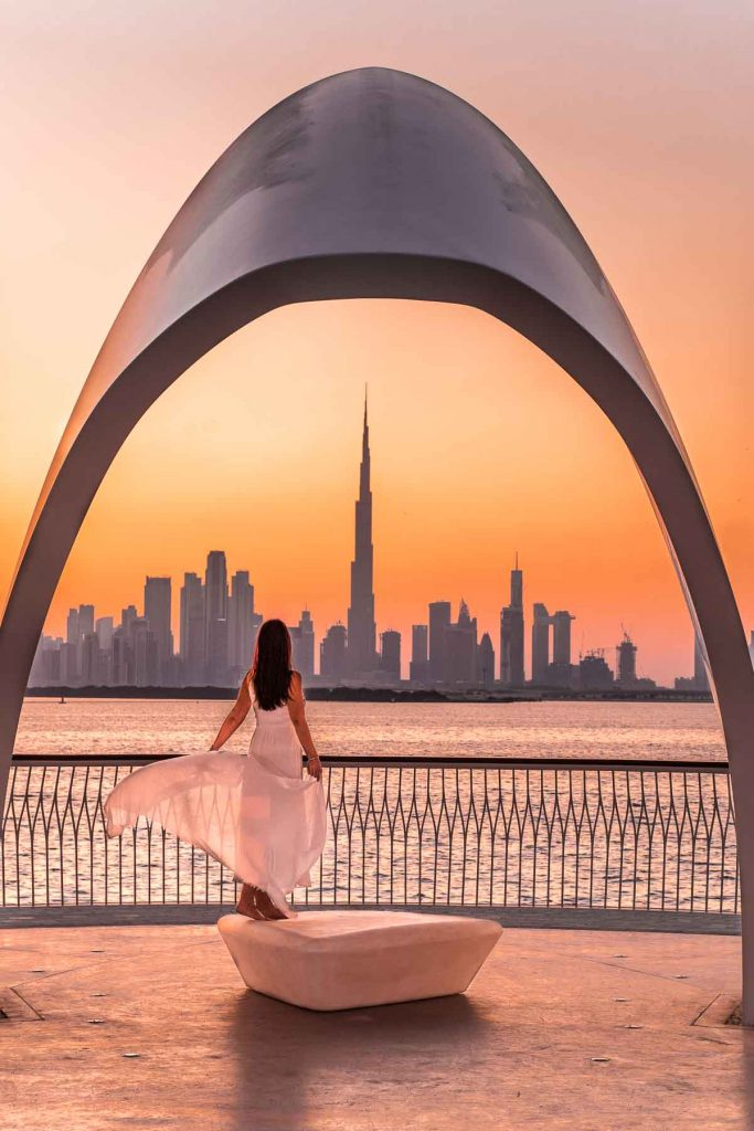 Girl in a white dress standing at the Dubai Creek Harbour at sunset (which is one of the most instagrammable places in Dubai)