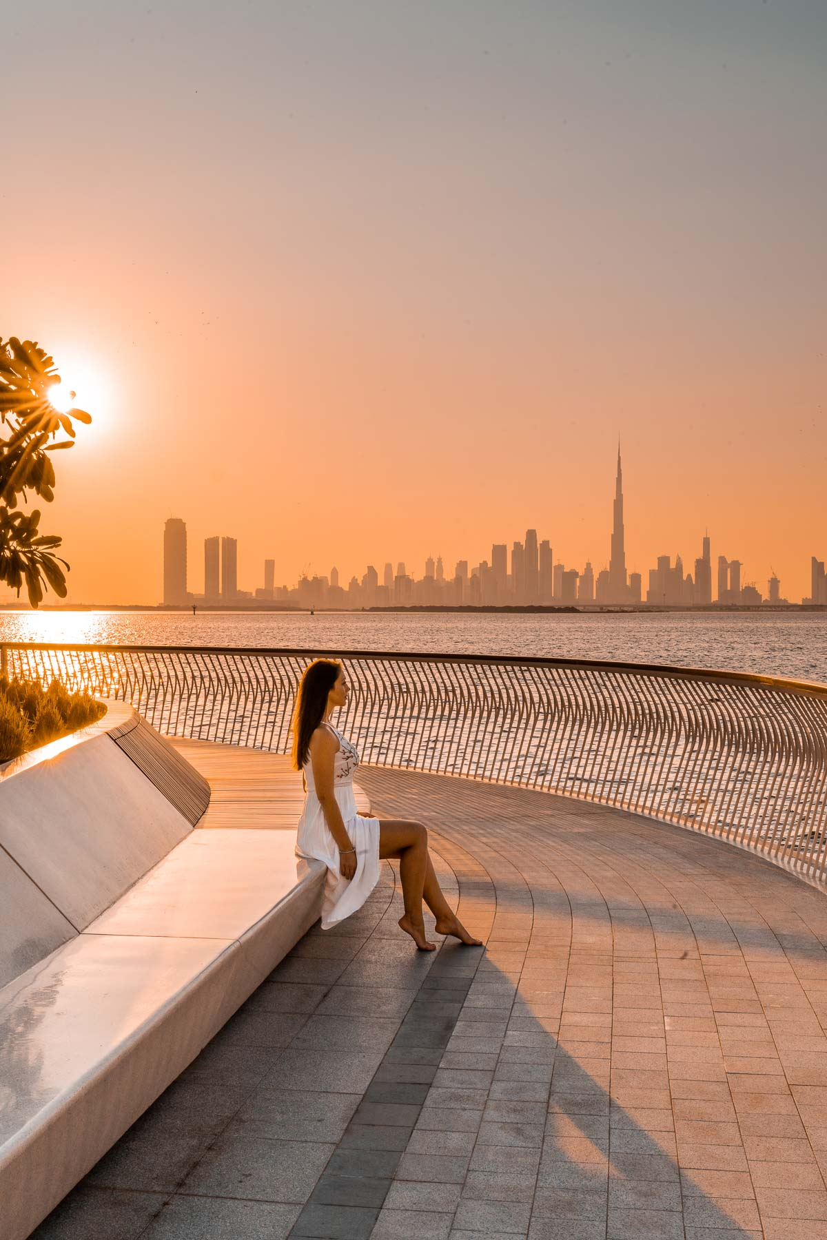 Girl in a white dress sitting at the Dubai Creek Harbour at sunset which is one of the most instagrammable places in Dubai