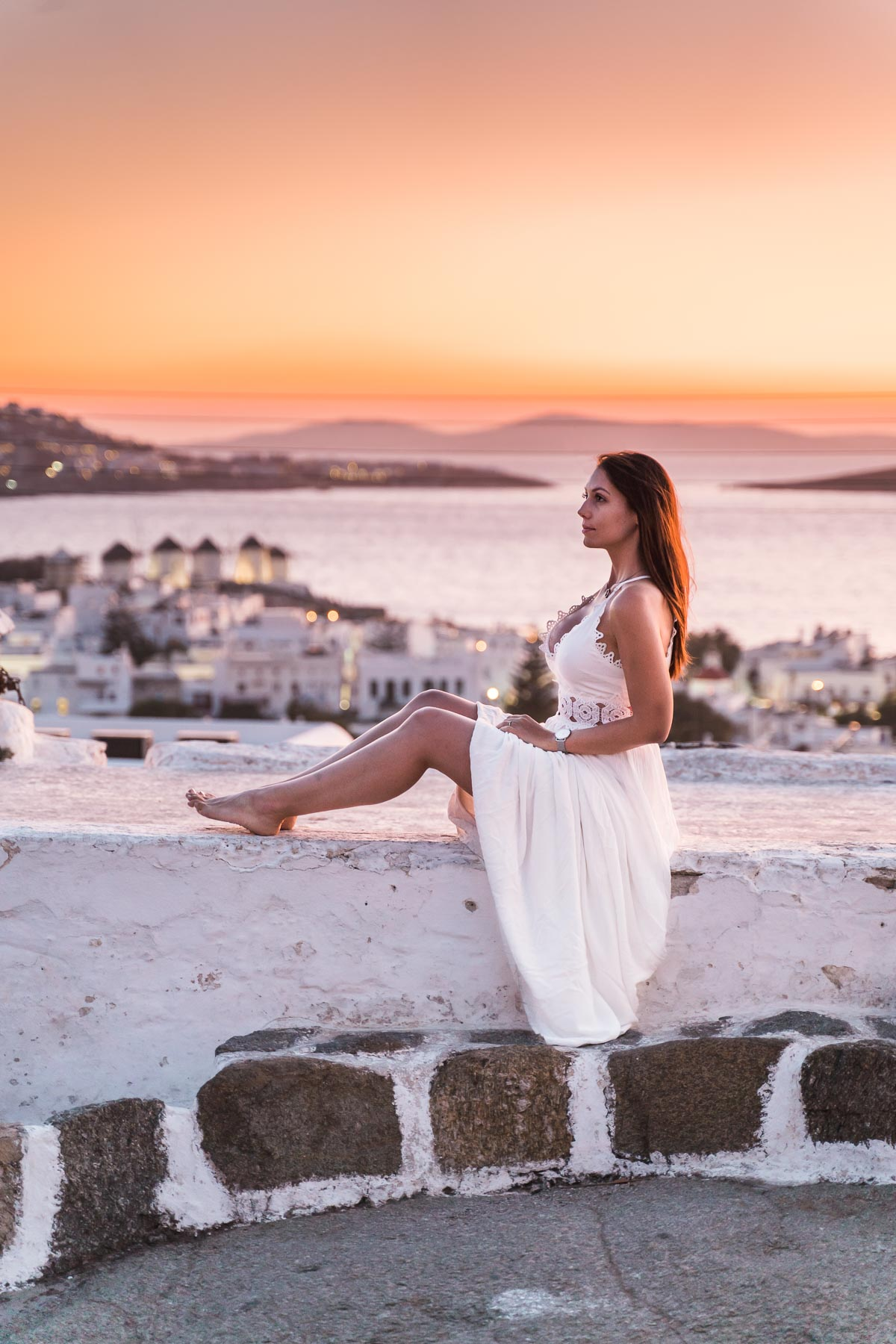 Girl in a white dress sitting on a wall at Boni's Windmill, watching the sunset over Mykonos Town