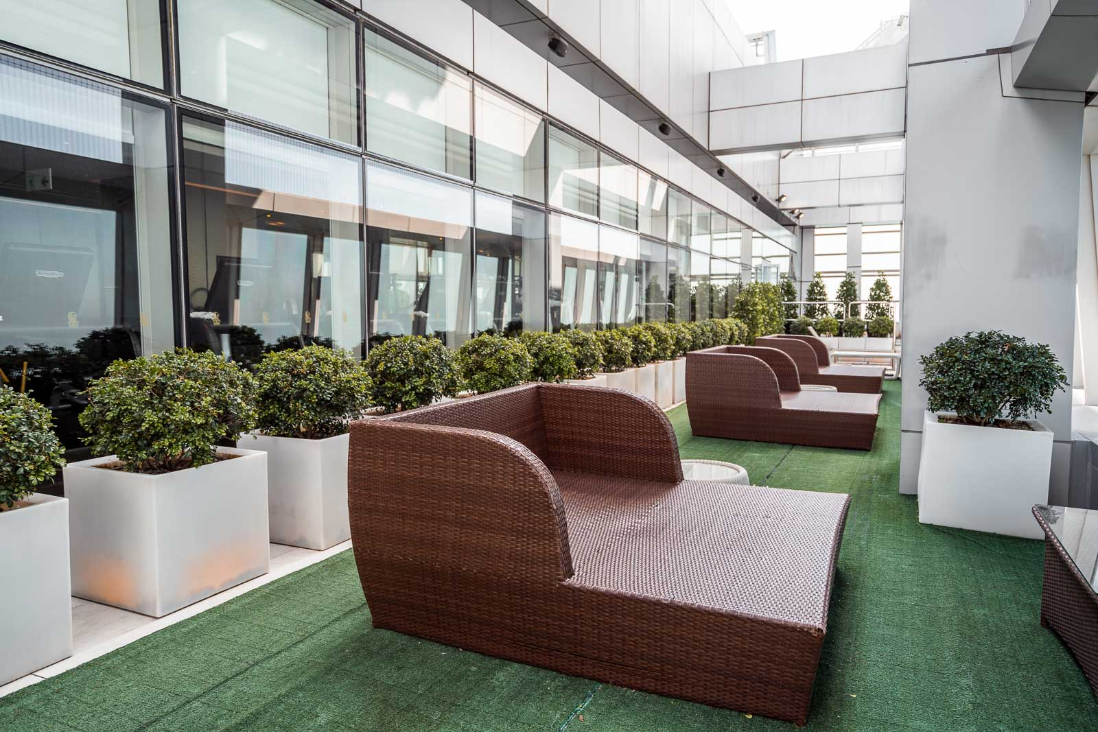 Outdoor terrace on the 118th floor with chairs and green plants