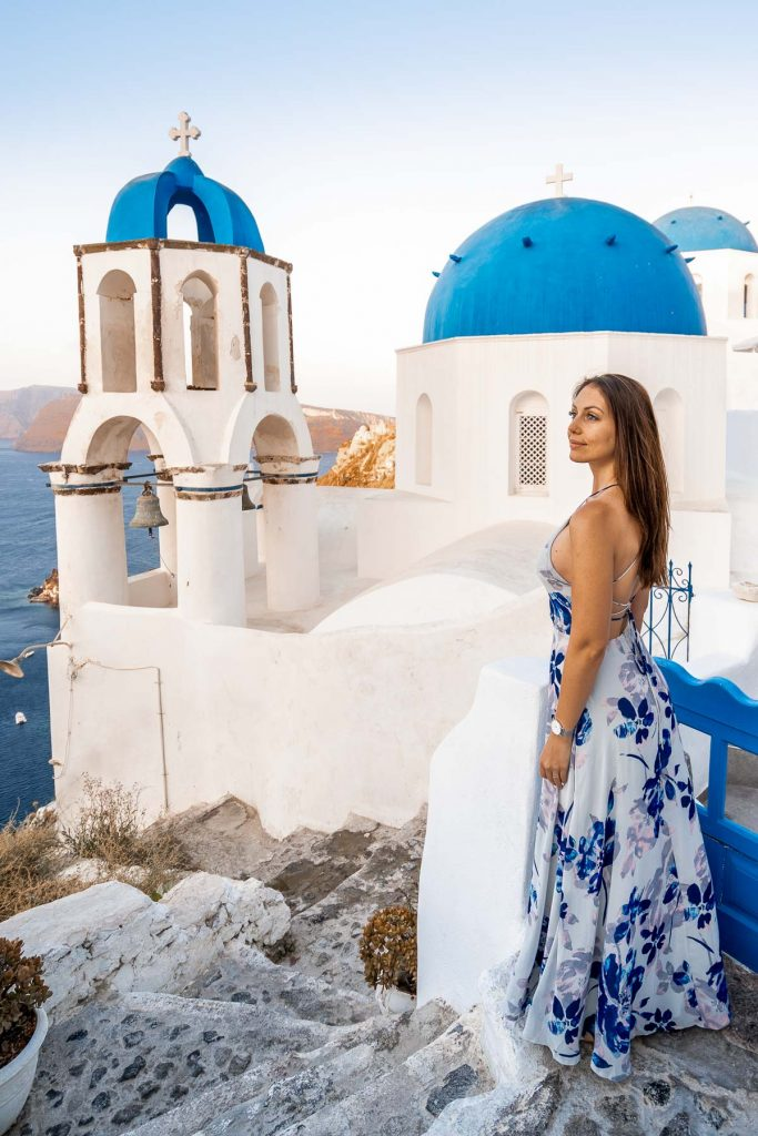 Girl in a blue dress standing in front of the three domes in Oia, Santorini