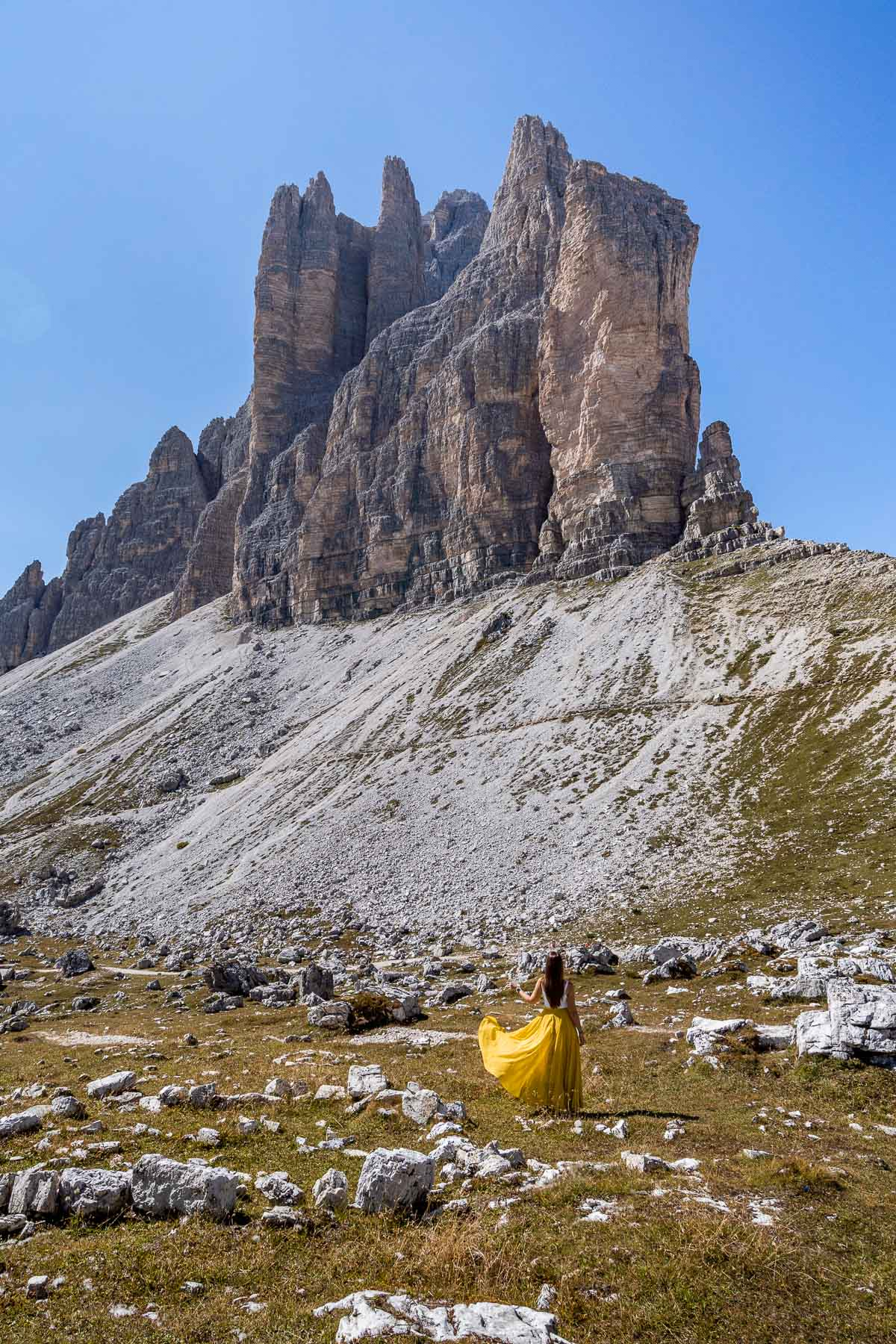 Girl in a yellow skirt twirling in front of the three peaks of Tre Cime di Lavaredo in the Dolomites
