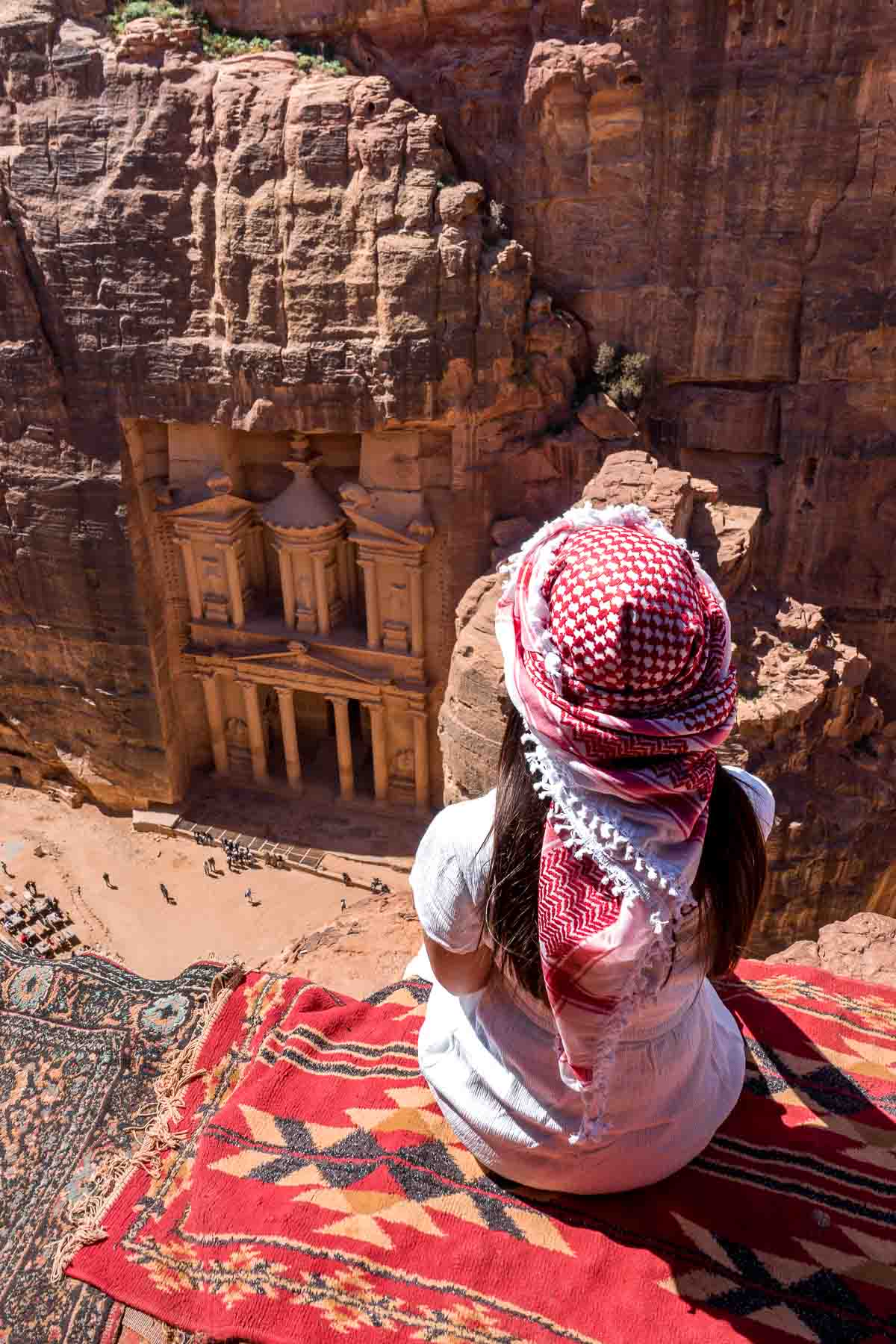 Girl in a white dress and a white-red keffiyeh sitting at the best Treasury viewpoint in Petra, Jordan